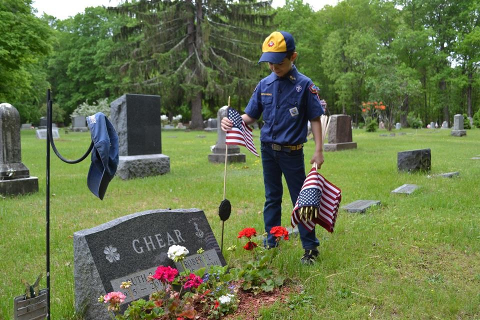 Joseph Sweeney is placing a flag on the grave of his Great Grandfather, Robert Ghear.