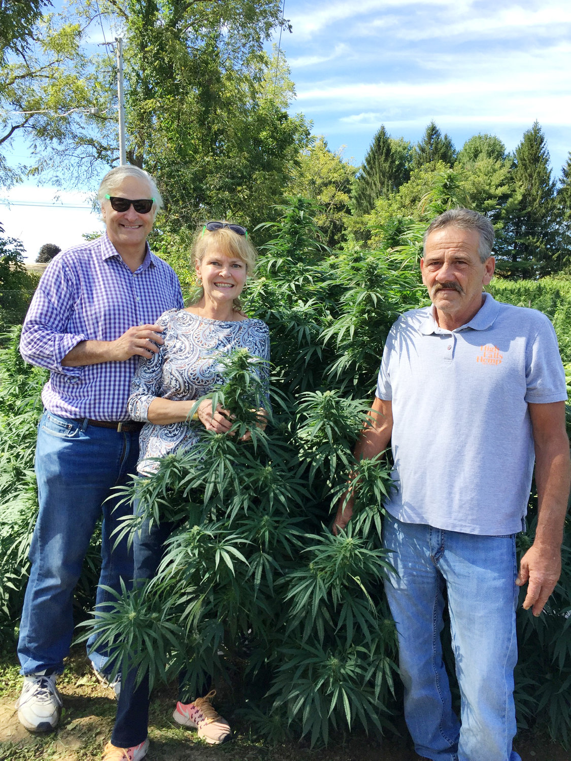 Rick Weissman, Tricia Horst and Kenny Oakley pose with a happy hemp plant.
