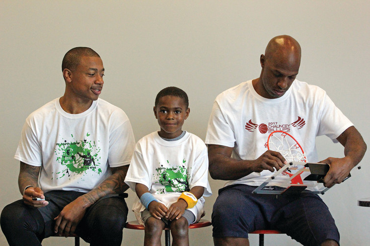 Boston Celtics star player Isaiah Thomas, left, looks on as A.J. Wertheimer, 6, prepares for a photo and Chauncey Billups finishes autographing Wertheimer's miniature basketball hoop. Academy participants received a photo with the NBA stars and an autographed item in addition to the skills they learned during the week.