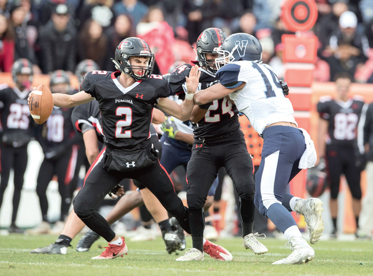 Pomona quarterback Ryan Marquez scrambles as teammate Kenny Maes tries to keep Valor Christian defender Christian Elliss away in last year's state title game, won by Valor.