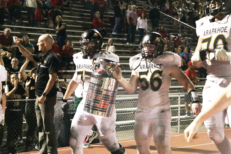 Arapahoe football players Blake Carrette (77) and Riley Schell (56) carry the Brookridge Trophy to their teammates and fans after the Warriors won the Sept 9 game with Heritage, 28-13.