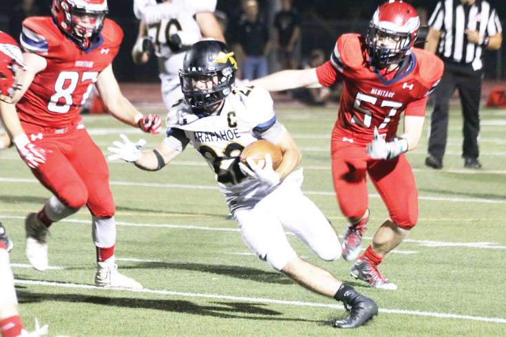Arapahoe senior Matt Phelan (22) cuts up the field as he seeks to elude Heritage defenders Phillip Ferguson (57) and Josh Rivera (77) during the Sept. 9 rivalry football game. Phelan scored a pair of touchdowns as the Warriors won the game, 28-13.
