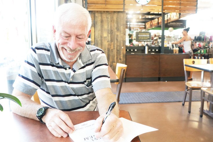"Steve Siegal autographs a copy of his second cop novel, ""Contra Legem – Against the Law."" The Littleton resident drew on many of his experiences as he spent 36 years in law enforcement including more than 30 years with the Englewood Police Department."