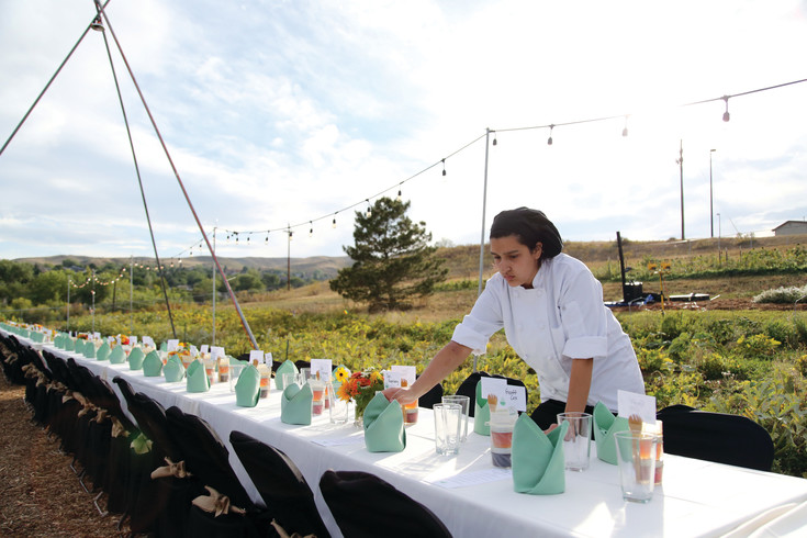 Warren Teach culinary student Miriam Garza double checks the place settings at the schools Farm to Table dinner Sept. 17.
