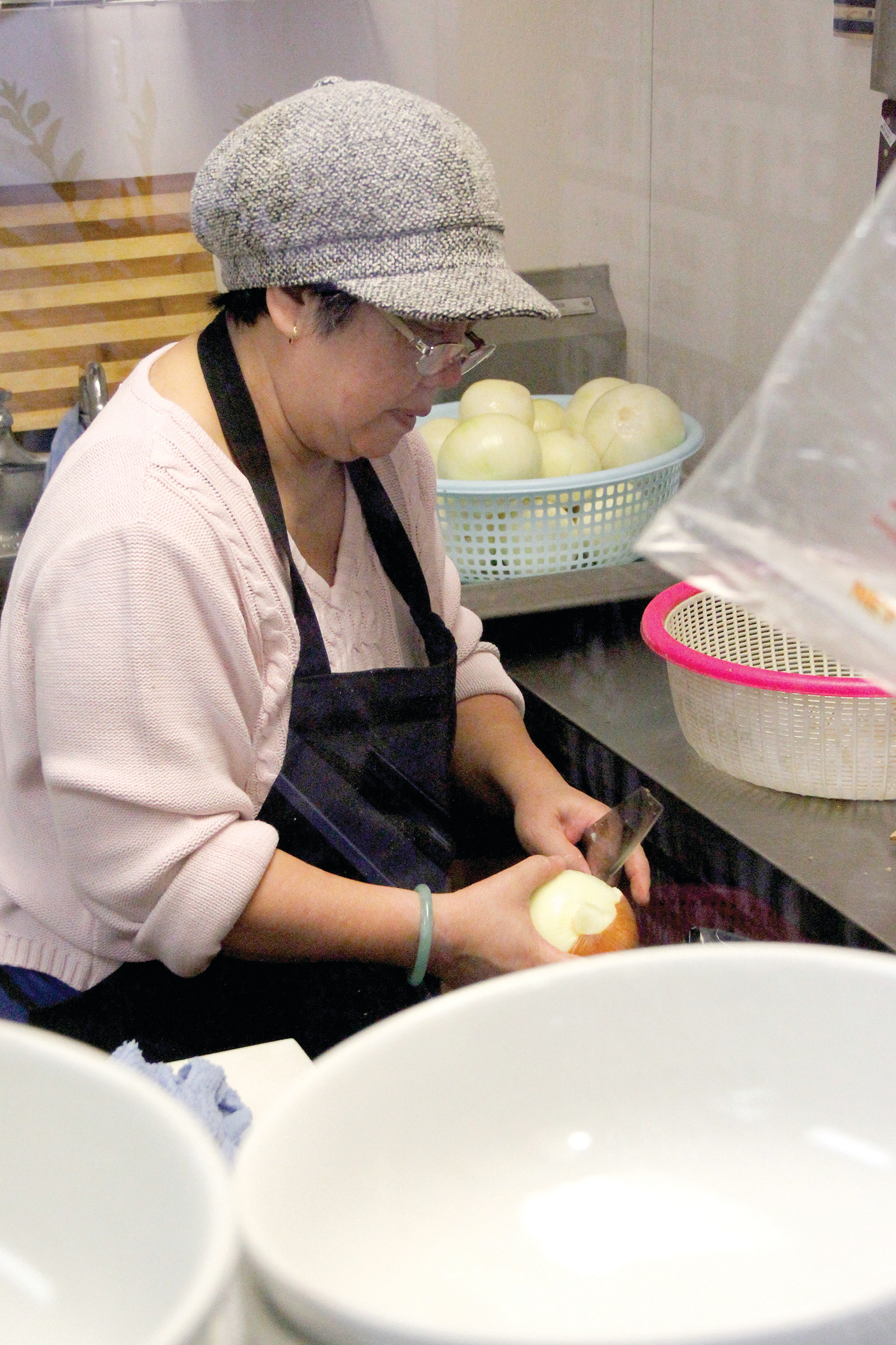 Dung Nguyen slices onions in the kitchen at Pho Real in Littleton. Customers and pho restauranteurs say using fresh ingredients is critical to a good bowl of pho.