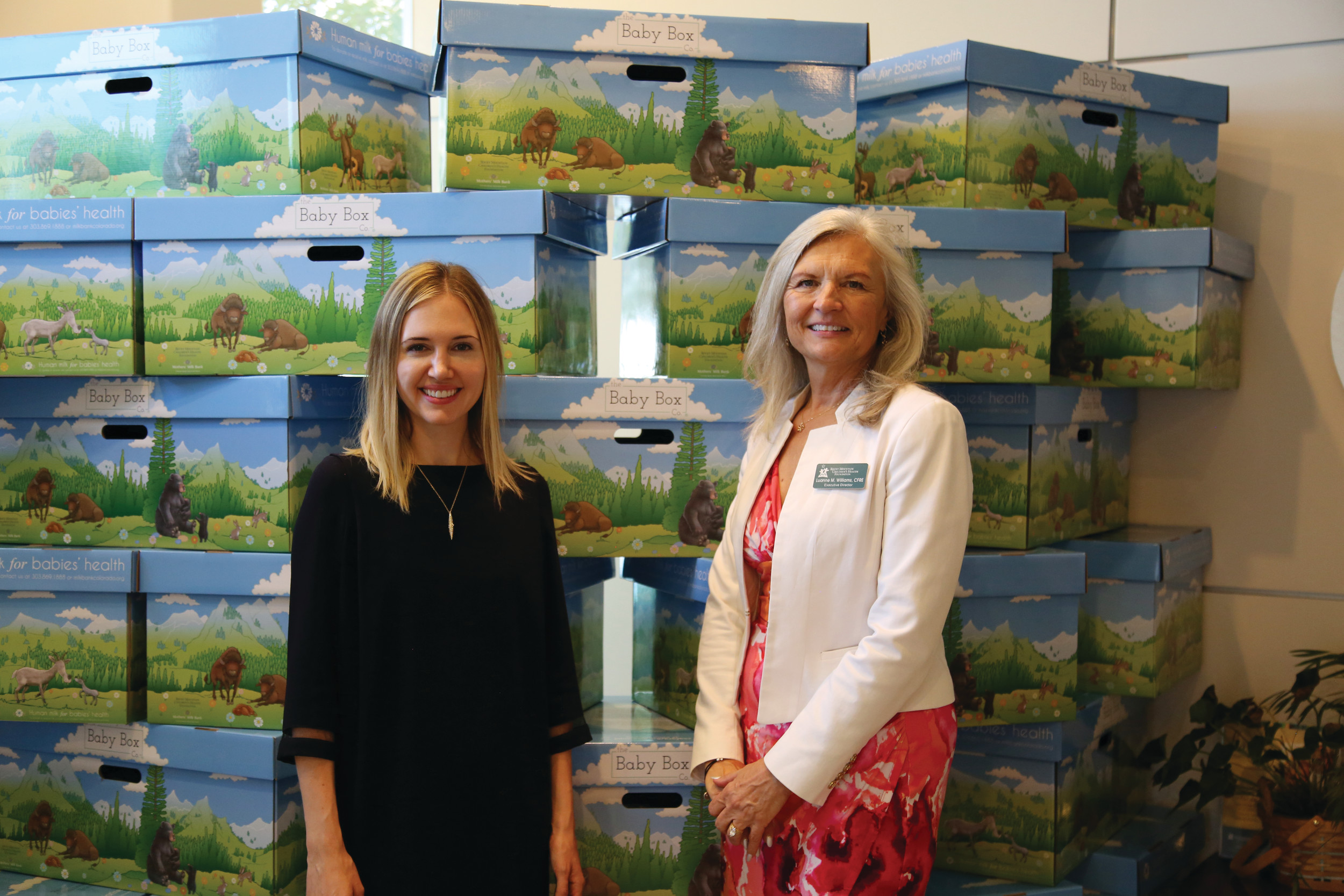 Michelle Vick, co-founder of The Baby Box Co., left, and Luanne Williams, executive director of Rocky Mountain Children's Health Foundation, stand in front of the first shipment of Baby Boxes for new Colorado parents.