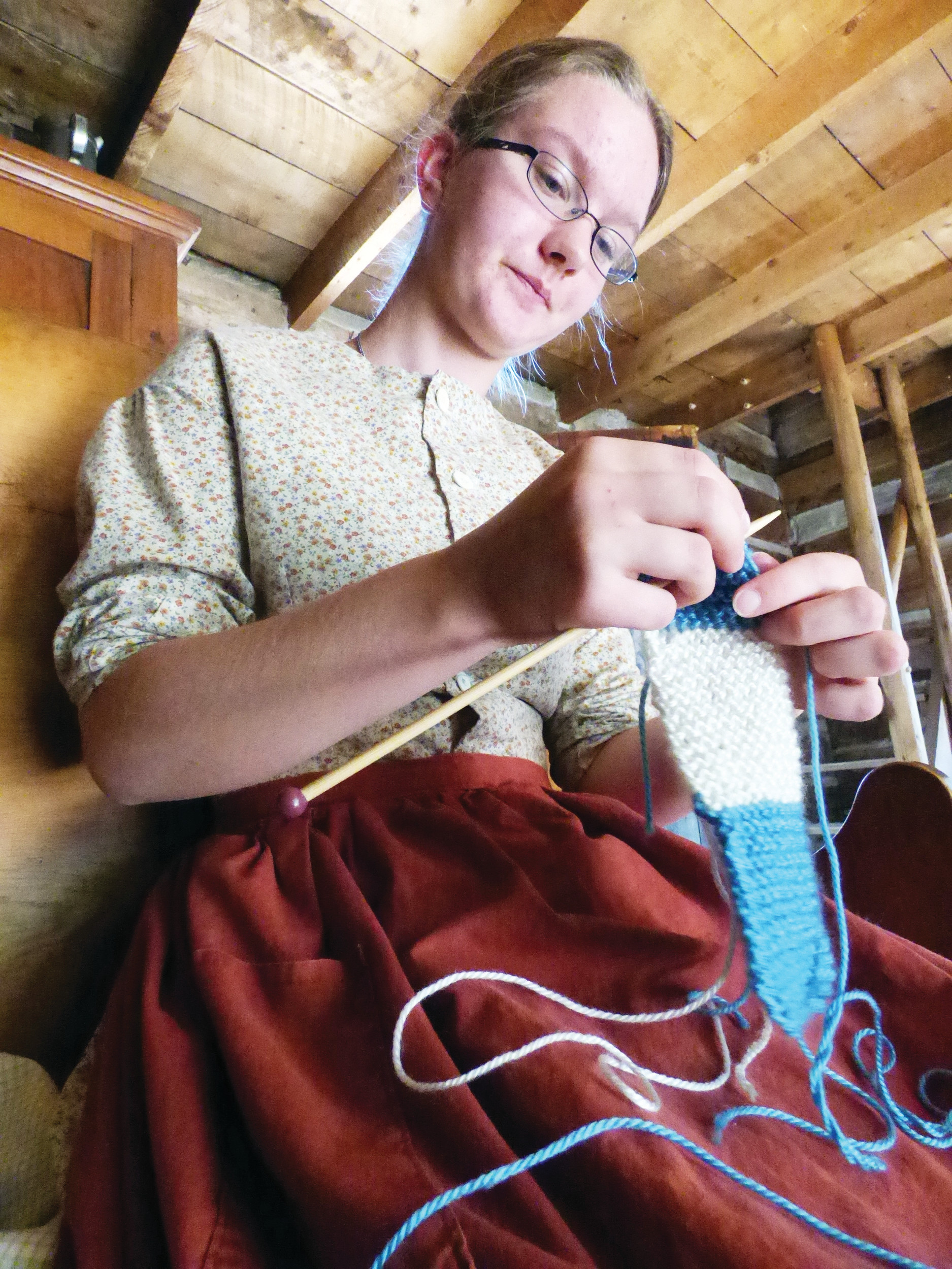 Mary Hathaway knits a scarf. Any down time on a pioneer homestead was filled with some useful task.