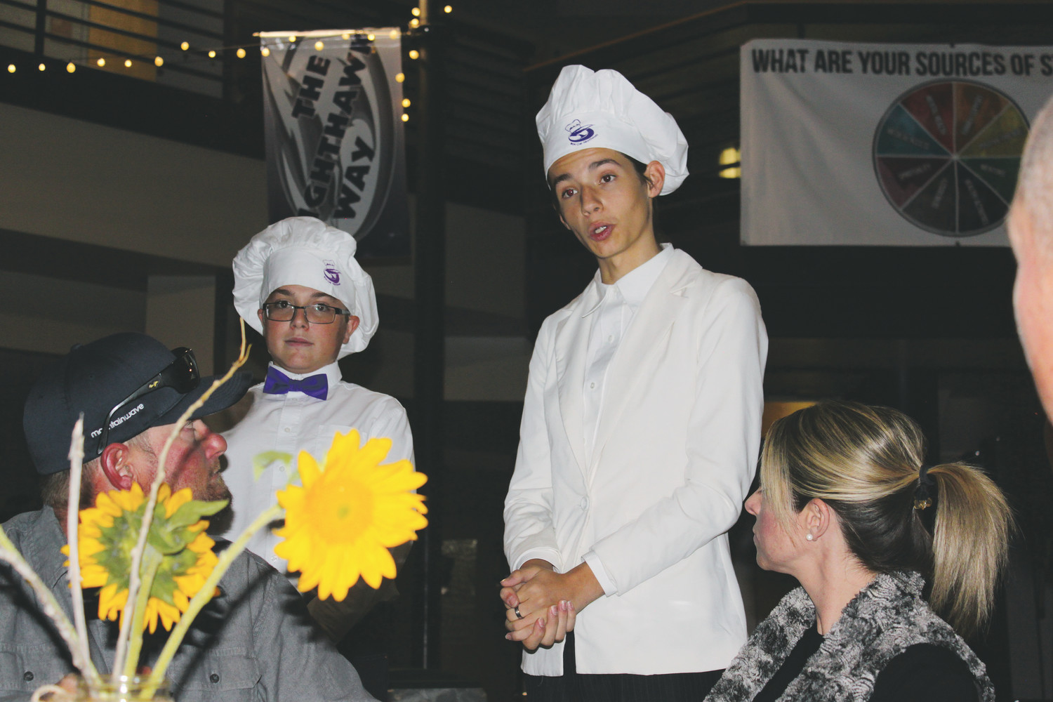 Austin Coudeyras, L, watches on as Brenden Bernsdorf recites the evening specials to attendees at the RHMS dinner.