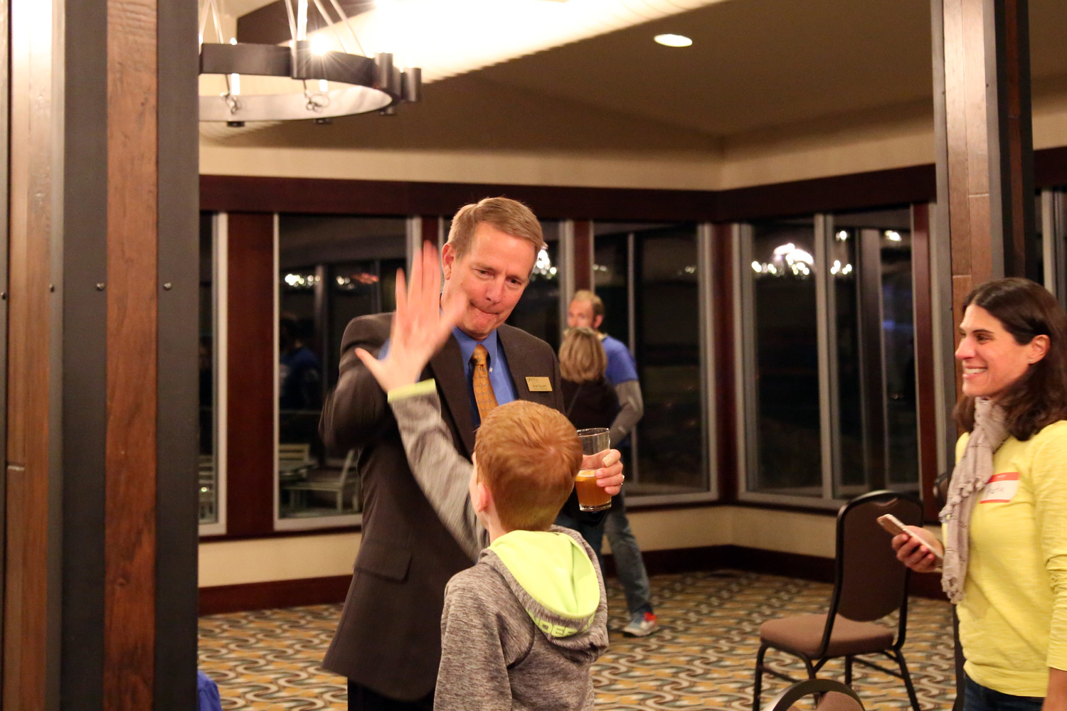 Jeffco Schools incumbent Brad Rupert gives a high five as his leading number come in during election night.