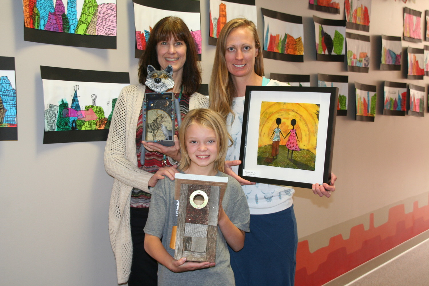 From left, Shelton's family engagement liaison Susan Kimes-Demboski and art teacher Amber BonDurant stand with fourth grader Stella Chesser holding art pieces the students purchased at this past summer's Cherry Creek Arts Festival. The festival's Janus Henderson Investors Student Art Buying Program provides students the opportunity to purchase artwork as a permanent installation for their school. The other students involved were sixth grader Will Lacey and first grader Caleb Griffin.