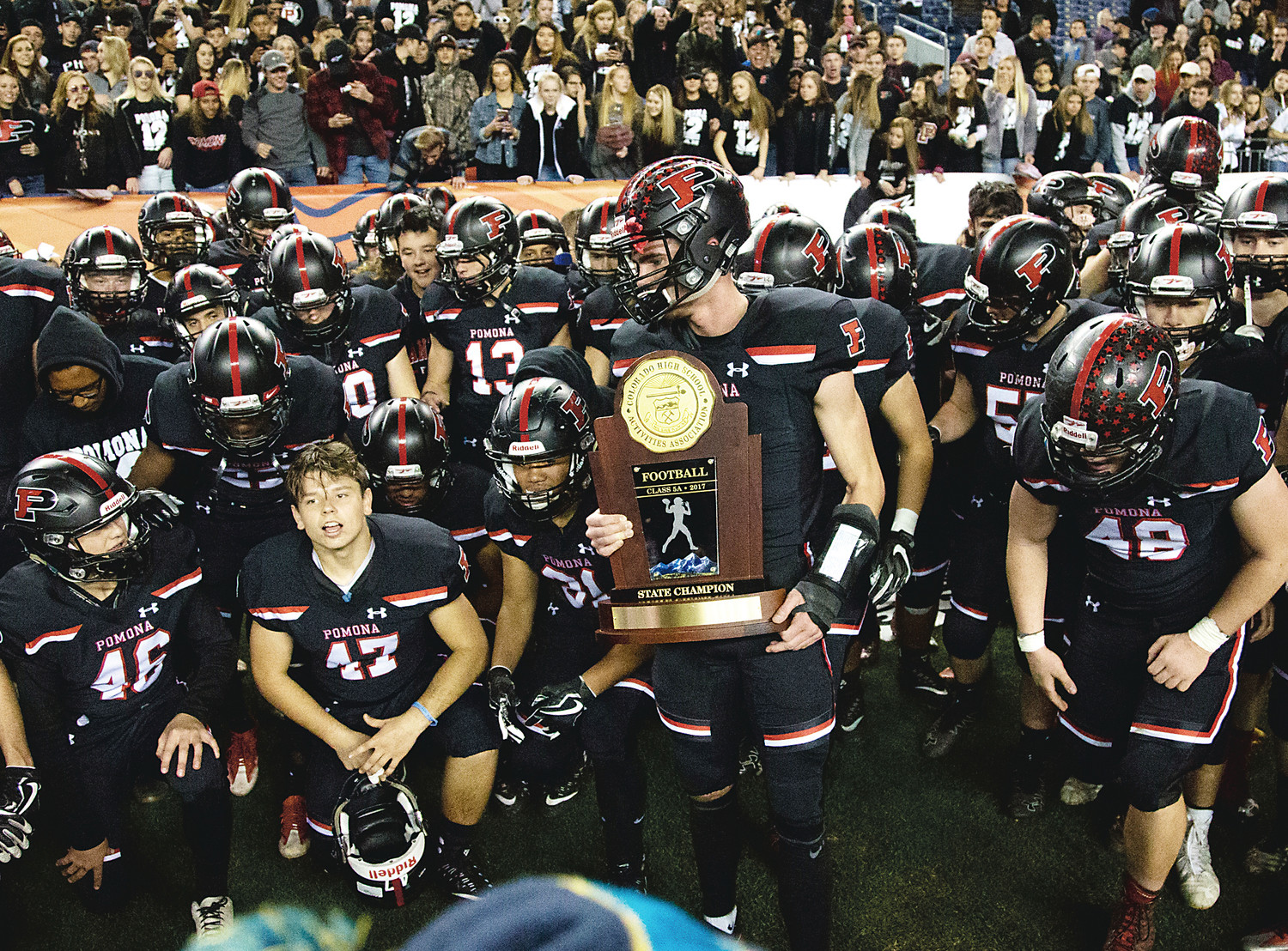 Below, Pomona senior quarterback Ryan Marquez holds on tight to the Class 5A football state championship trophy as the Panthers get ready to poise for a team photo after the win.