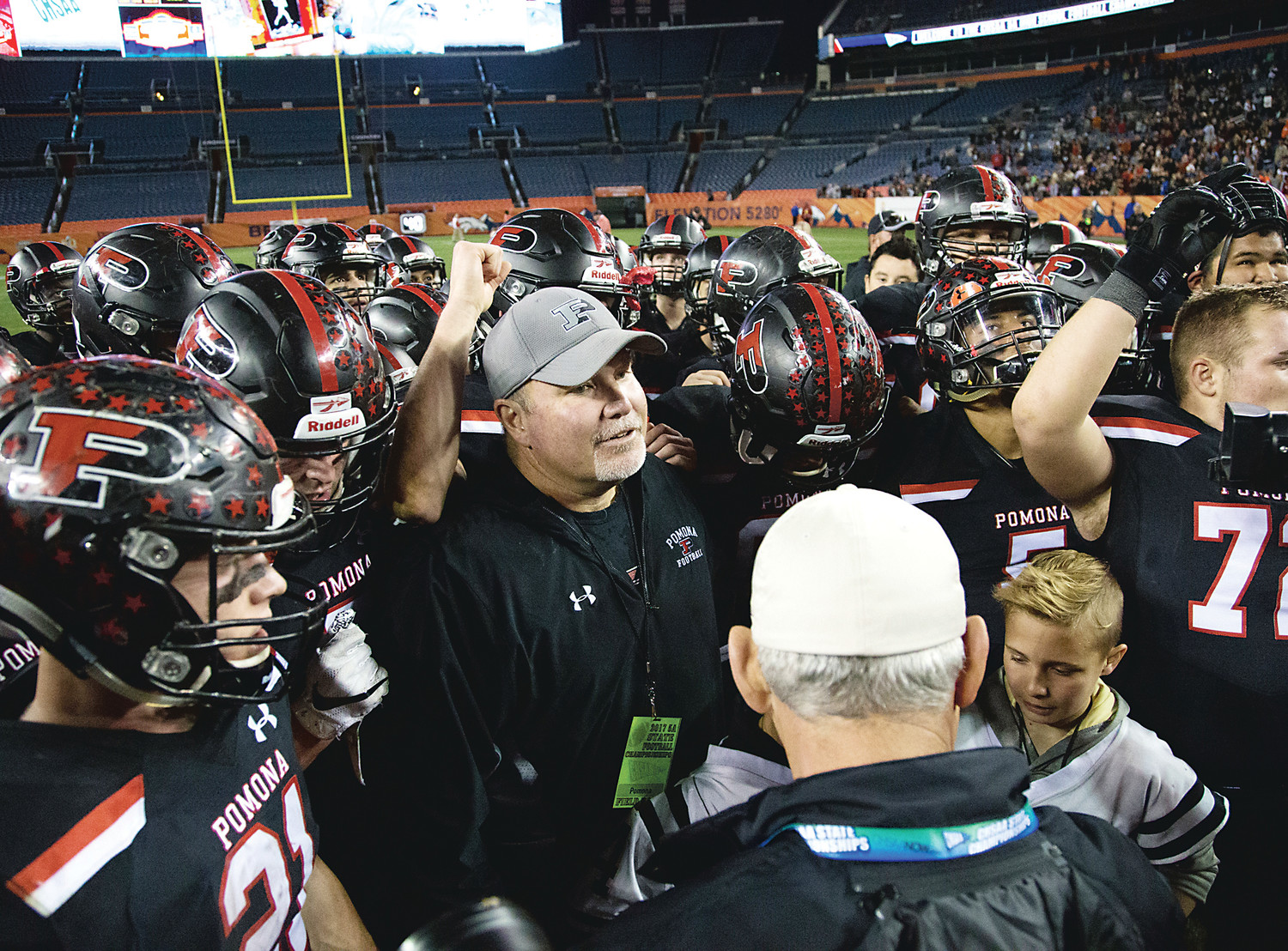 Pomona coach Jay Madden is surrounded by his players after the Panthers' 56-49 victory over Eaglecrest on Dec. 2 at Mile High Stadium. The game was the highest scoring Class 5A football state championship game in the state's history.