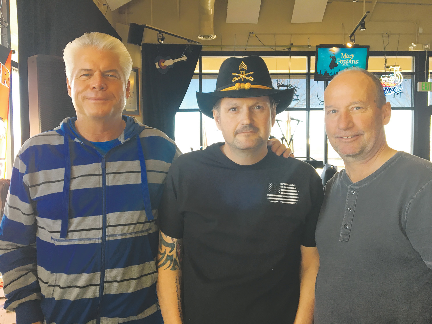 Ron Meier, left, and Bob Nobles, right, organized a fundraiser Dec. 9 at Takoda Tavern in Parker to help retired police officer and veteran Christian Redman with medical and living expenses. Redman is battling an aggressive form of colon cancer.
