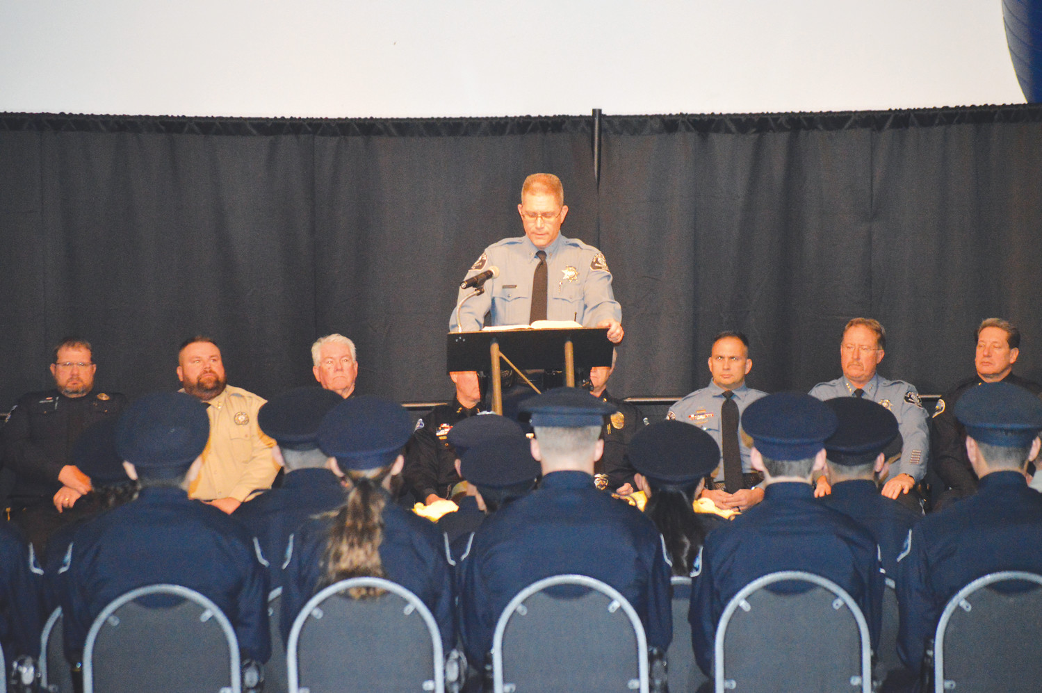 Brian Thompson, lead chaplain for Prairie Community Church in Firestone, Colo., leads the invocation prayers Dec. 7 at the Adams County Fairgrounds in Brighton as the 22nd class of the Adams County Sheriff's Academy graduated.