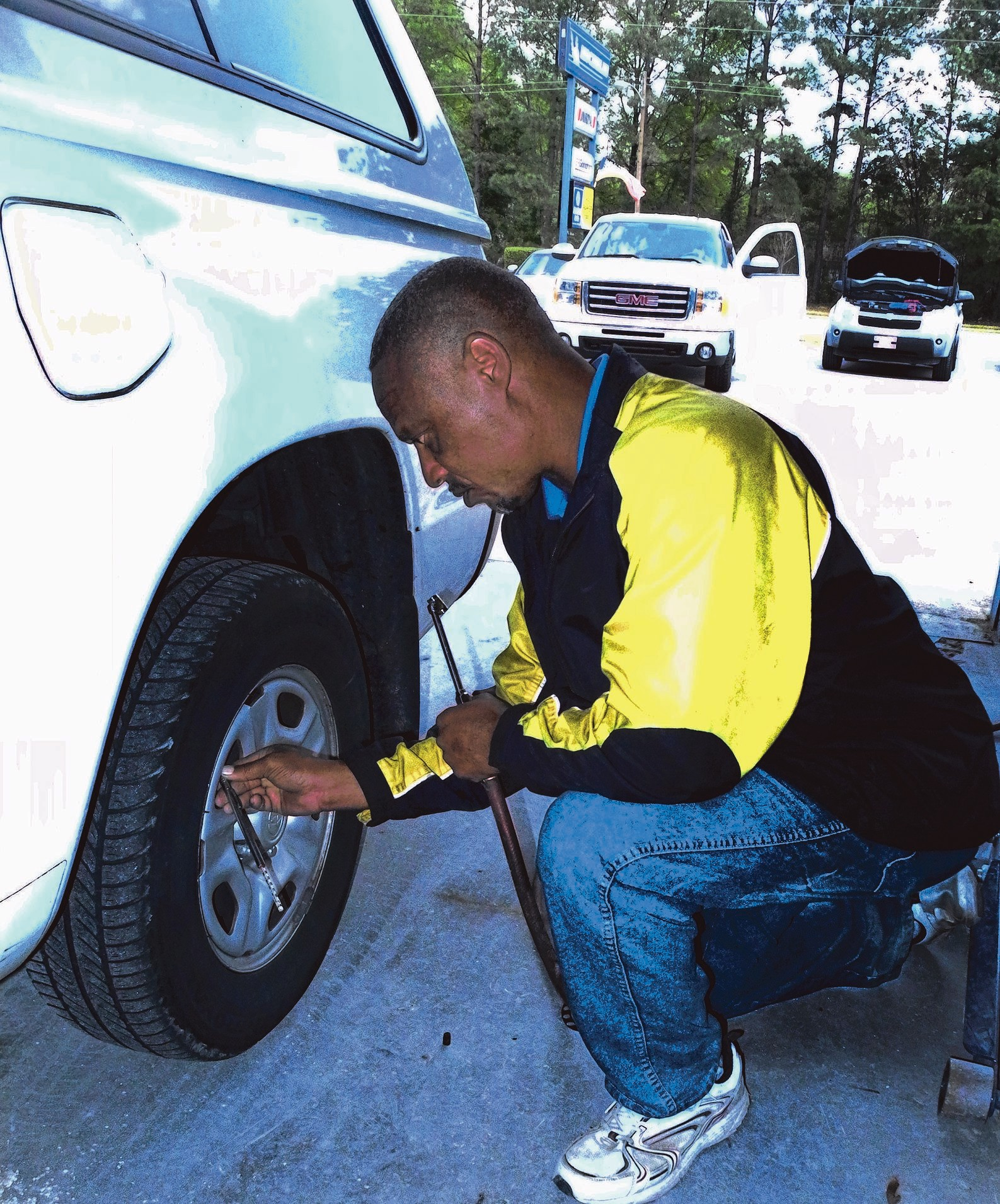 Eric Conyers with Ace Parker Tires checks a customer's tire recently. Air pressure in tires can affect gas mileage significantly and should be checked before Labor Day travel.