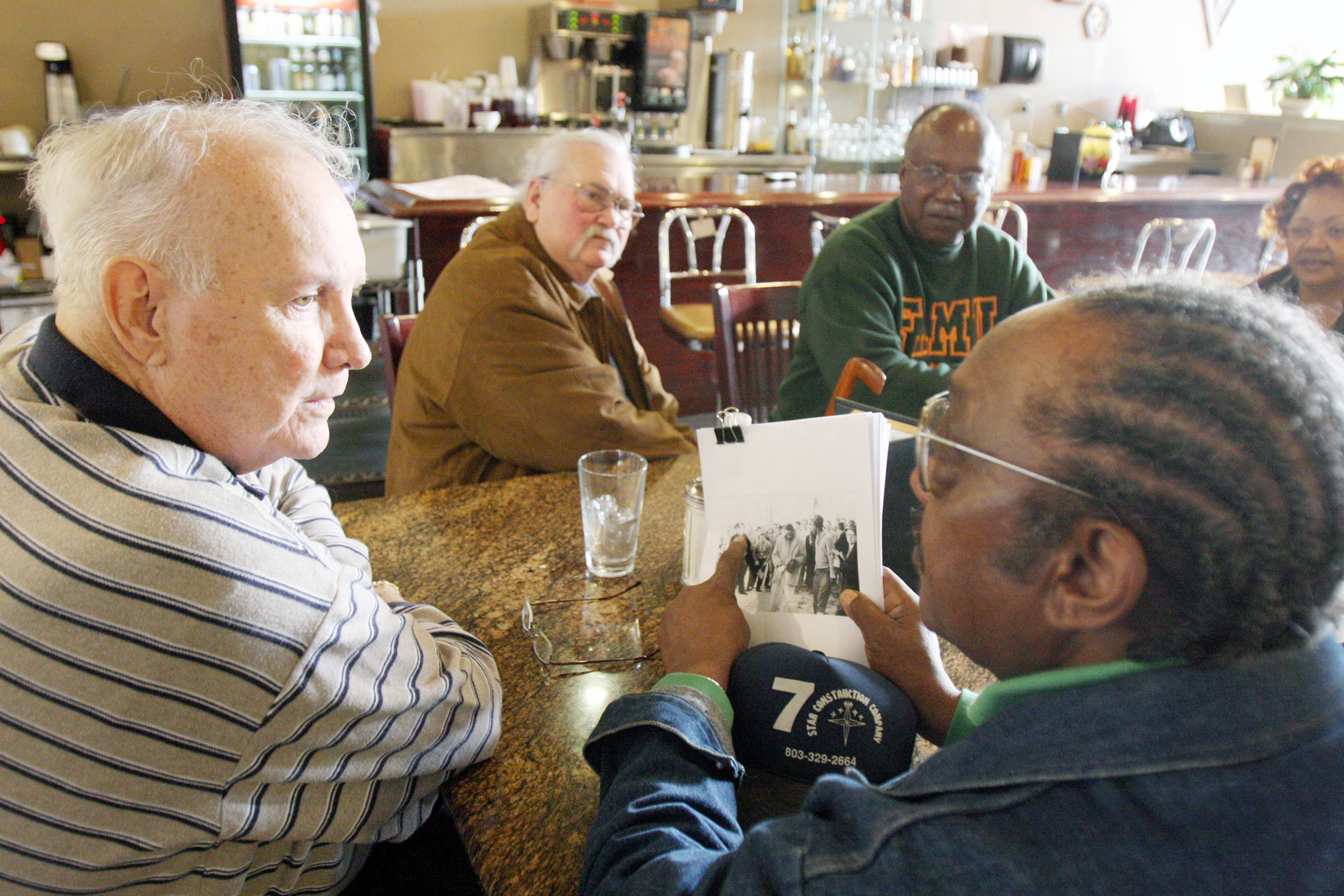 Elwin Wilson, left, and Friendship 9 member Willie McCleod, right, look over pictures from civil rights incidents in Rock Hill in the 1960s. James Wells, a member of the civil rights protest group, died Sunday at 77.