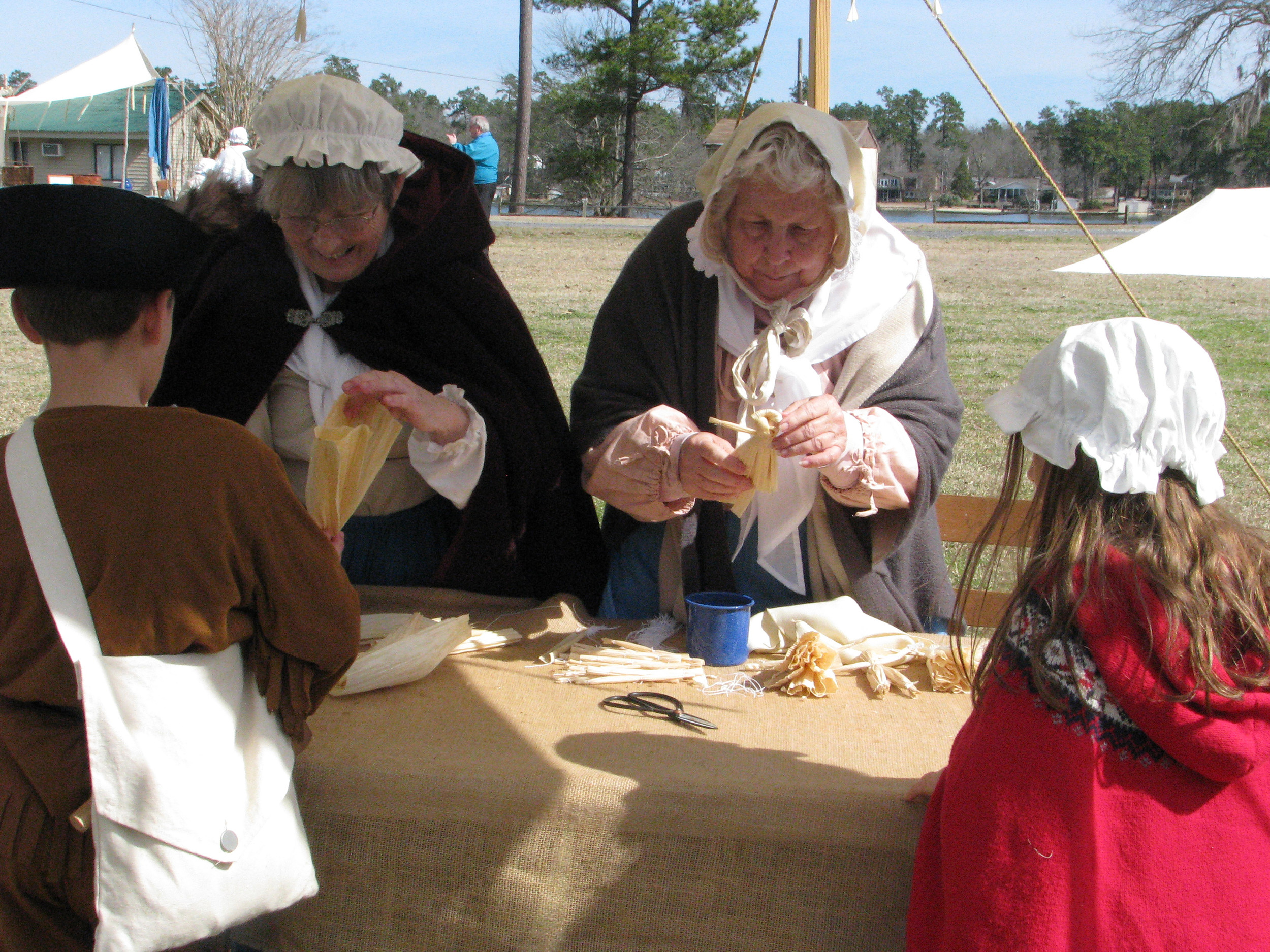 PHOTO PROVIDED  Pat Paul, left, and June Brailsford make corn husk dolls with children at last year's Francis Marion Living History Days. This year's event will be held at Camp Bob Cooper in Summerton on Feb. 27-28.