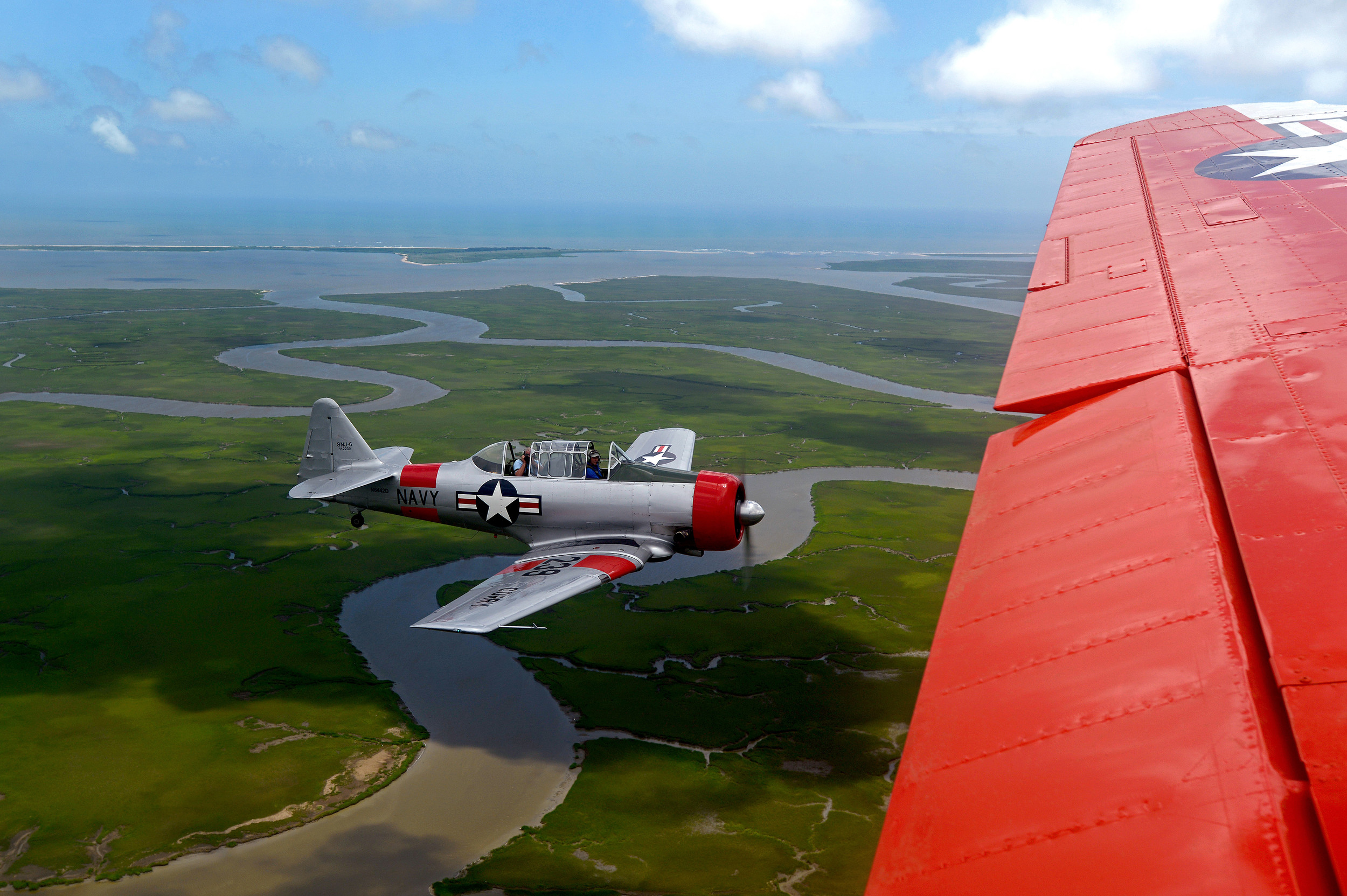A T-6 Texan flies beside a retired Navy C-45 during the Fourth of July's Salute from the Shore air parade on the coast of South Carolina on July 4, 2013.