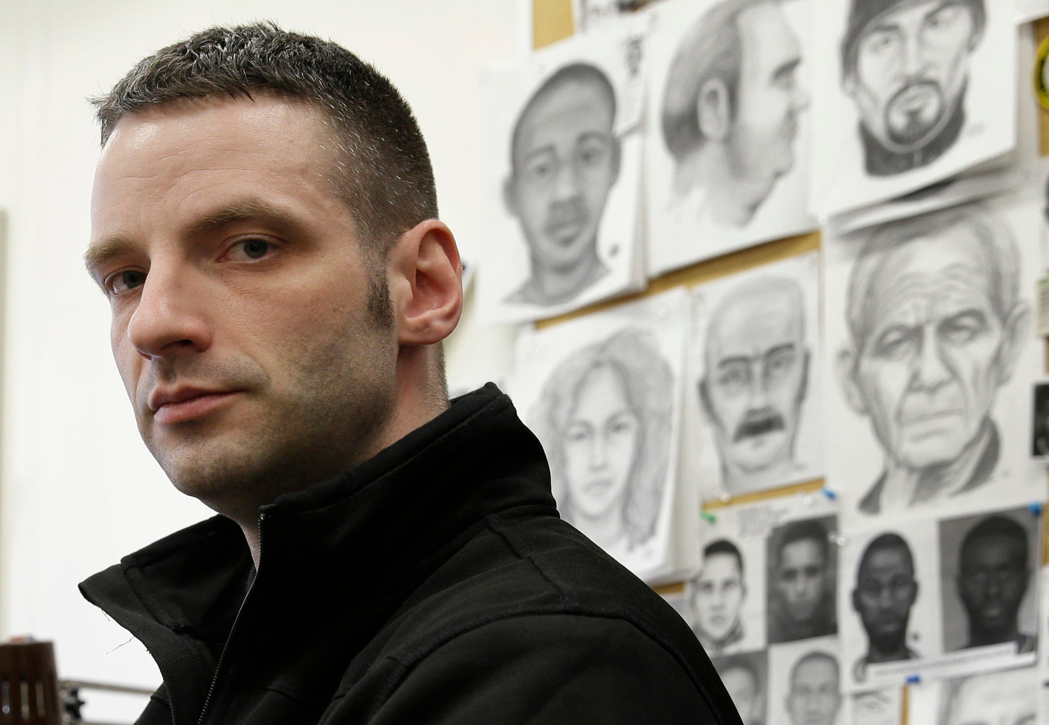 THE ASSOCIATED PRESSPolice officer Matthew Klein poses for a picture at his desk in the New York Police Department Artist Unit in New York. There are only about 100 full-time forensic artists left in the United States. Law enforcement officials say the work remains valuable because surveillance cameras and bystander cellphones can't be everywhere.