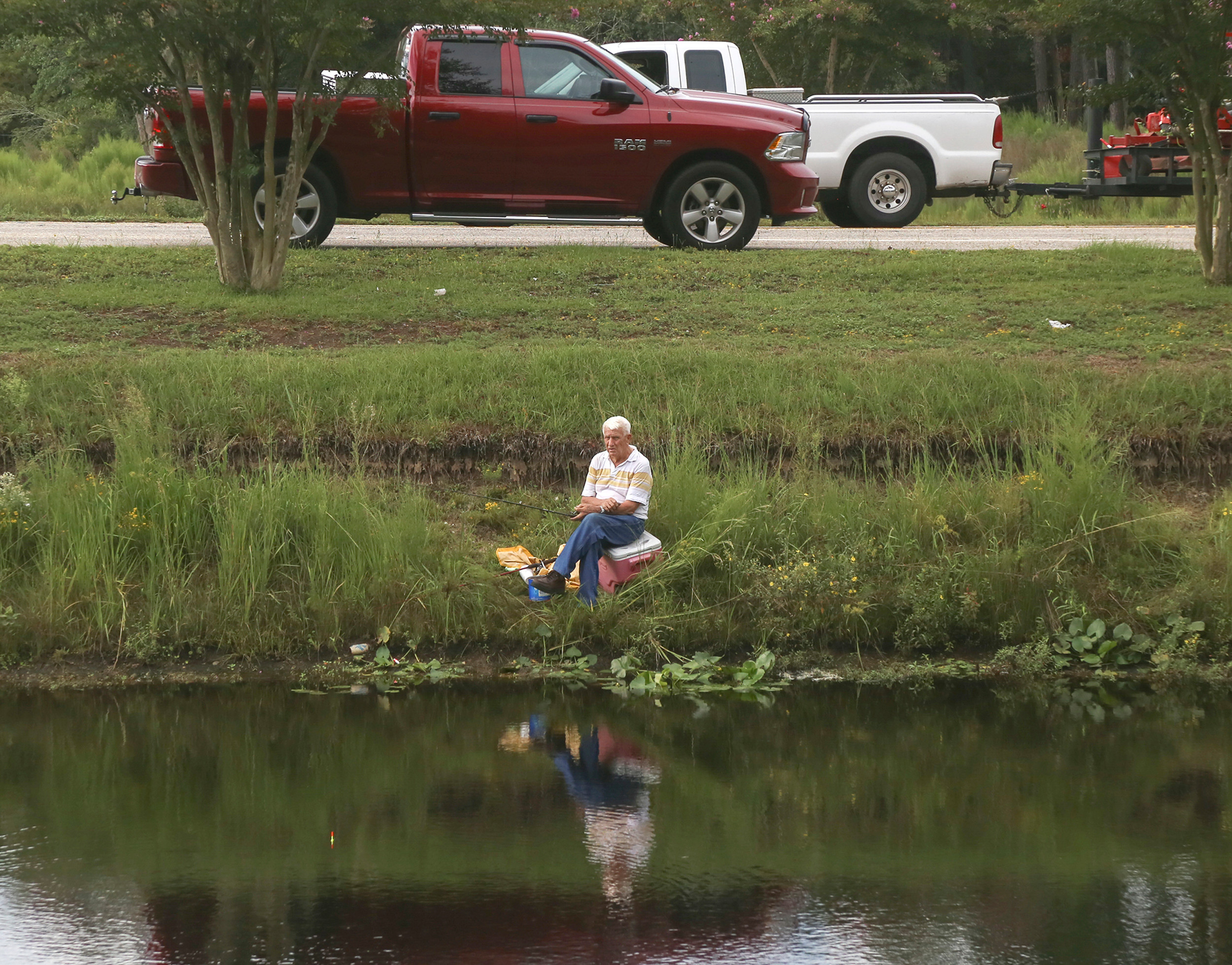 SUMTER ITEM FILE PHOTOA man enjoys an afternoon fishing on Second Mill Pond as traffic rushes by. County council passed an amendment to add the purchase of automated spillway gates for the dam at Second Mill Pond.