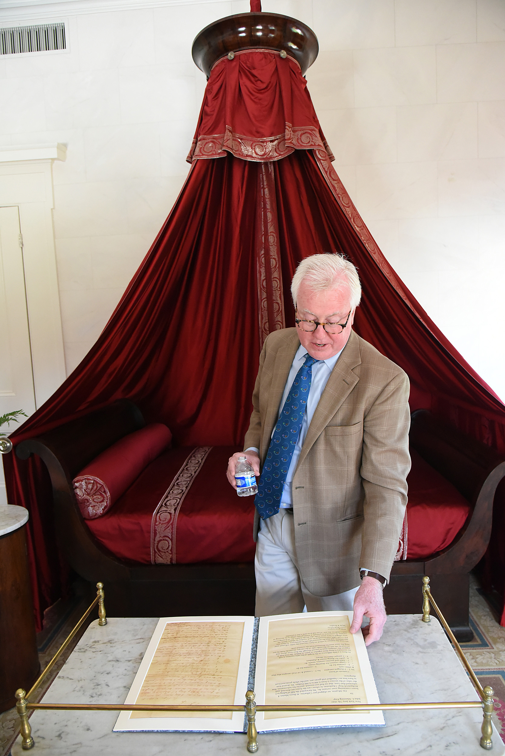 Peter Kenny, co-president of Classical American Homes Preservation Trust, explains the history of a bedroom that includes detailed written notes about the furniture in the room including the bed behind him.