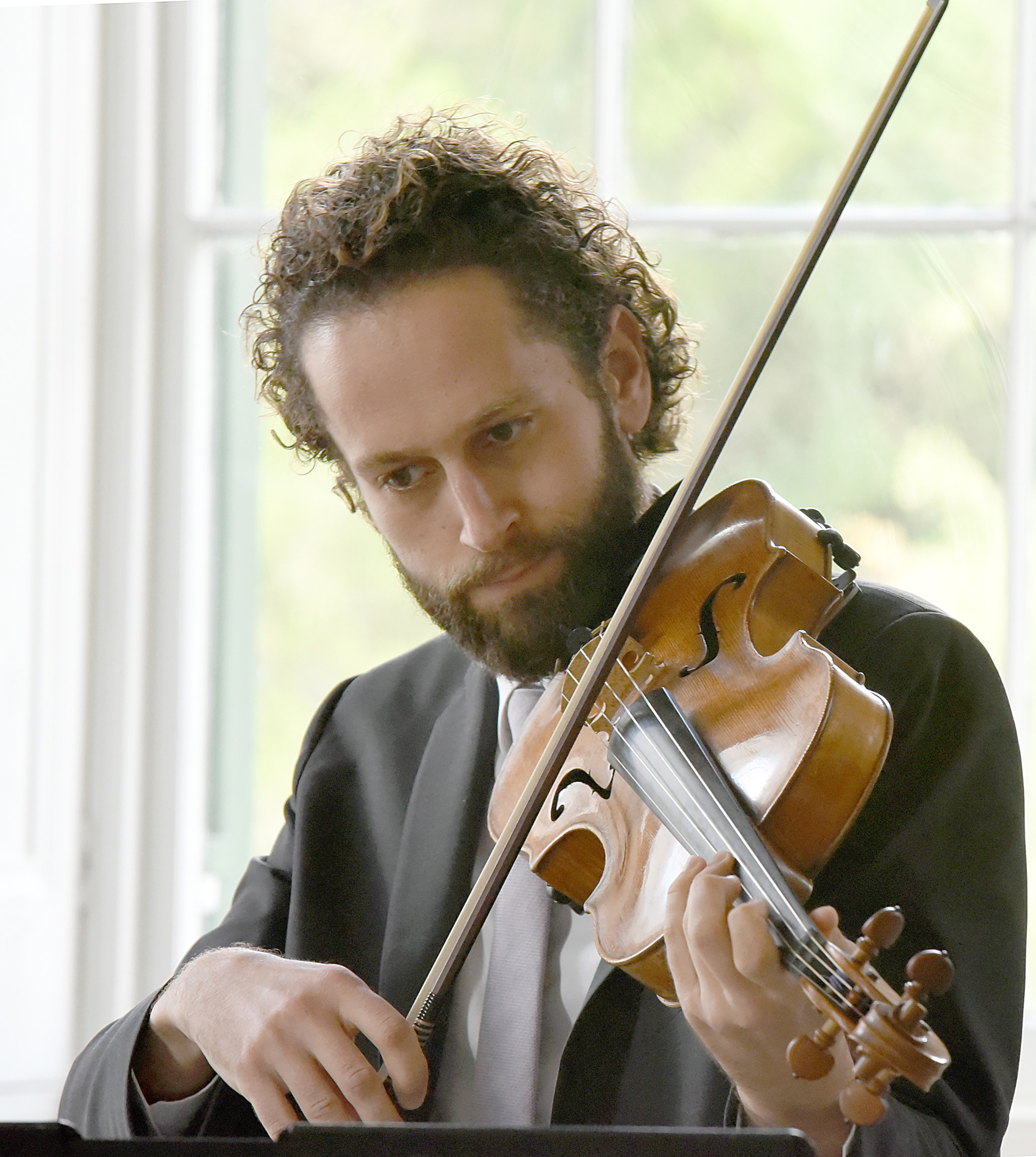 Ben Ullery, an assistant principal viola of the Los Angeles Philharmonic, focuses on performing a piece by Samuel Coleridge-Taylor during the string trio's performance at Millford Plantation.