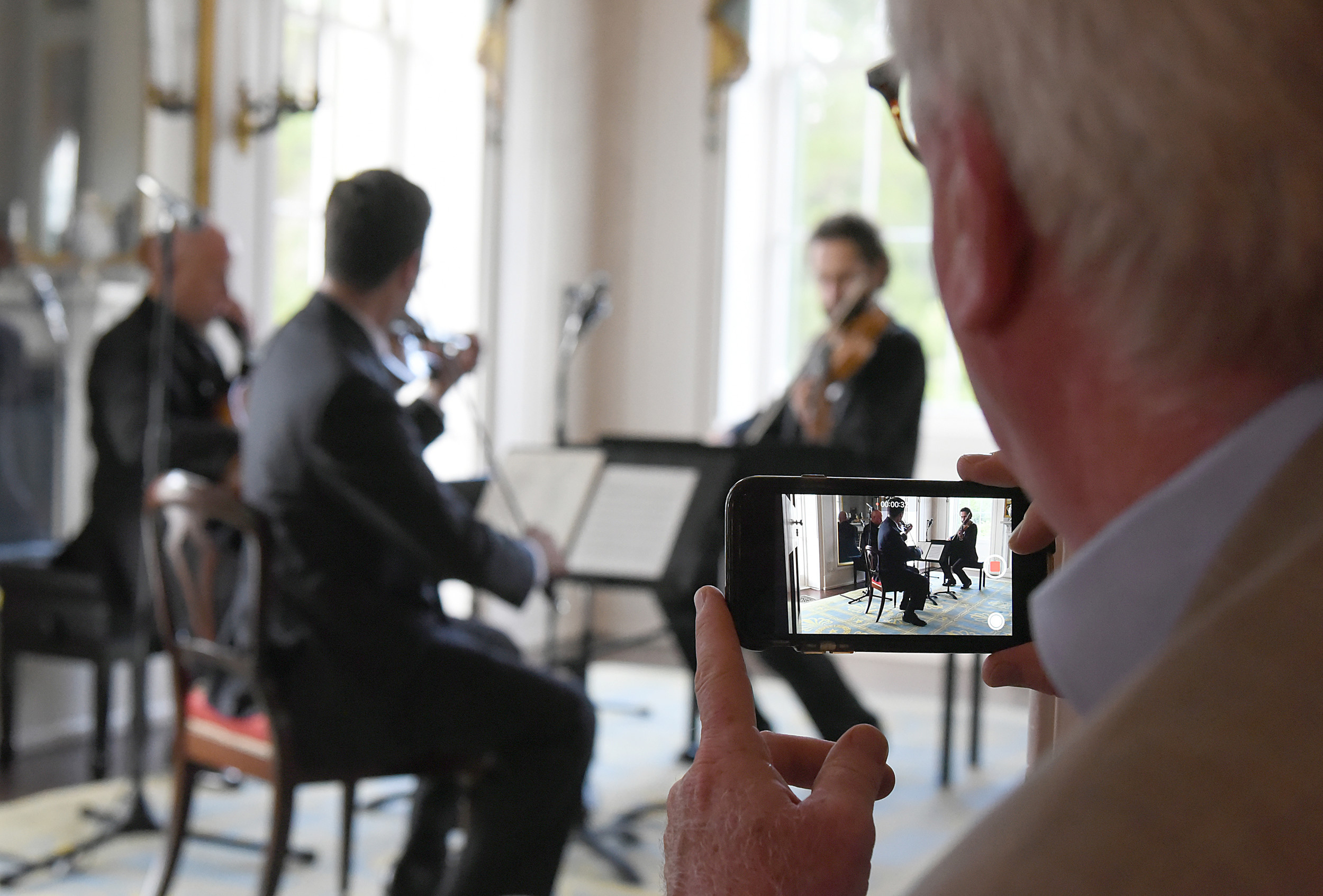 Co-president of the Classical American Homes Preservation Trust Peter Kenny uses a cellphone to record a video performance of the Los Angeles Philharmonic string trio during a performance Sunday at Millford Plantation.