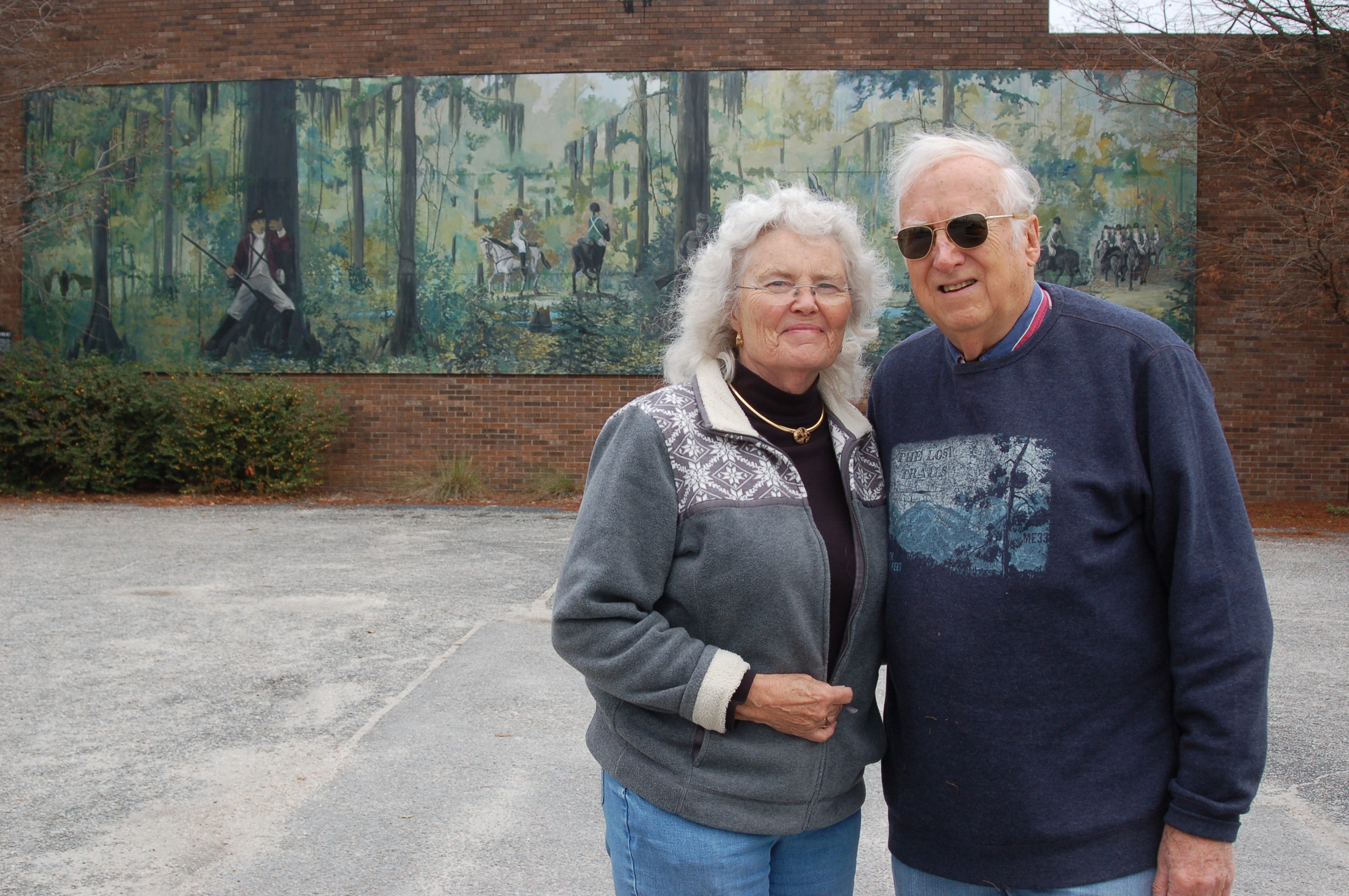 "Carole and George Summers, founders of the Swamp Fox Murals Trail Society, stand in front of the first American Revolutionary War mural completed in Clarendon County in 2001. The mural depicts the ""Swamp Fox at Ox Swamp"" and is located at the Manning Fire Department building. The mural was painted by Stateburg resident Will Anderson."