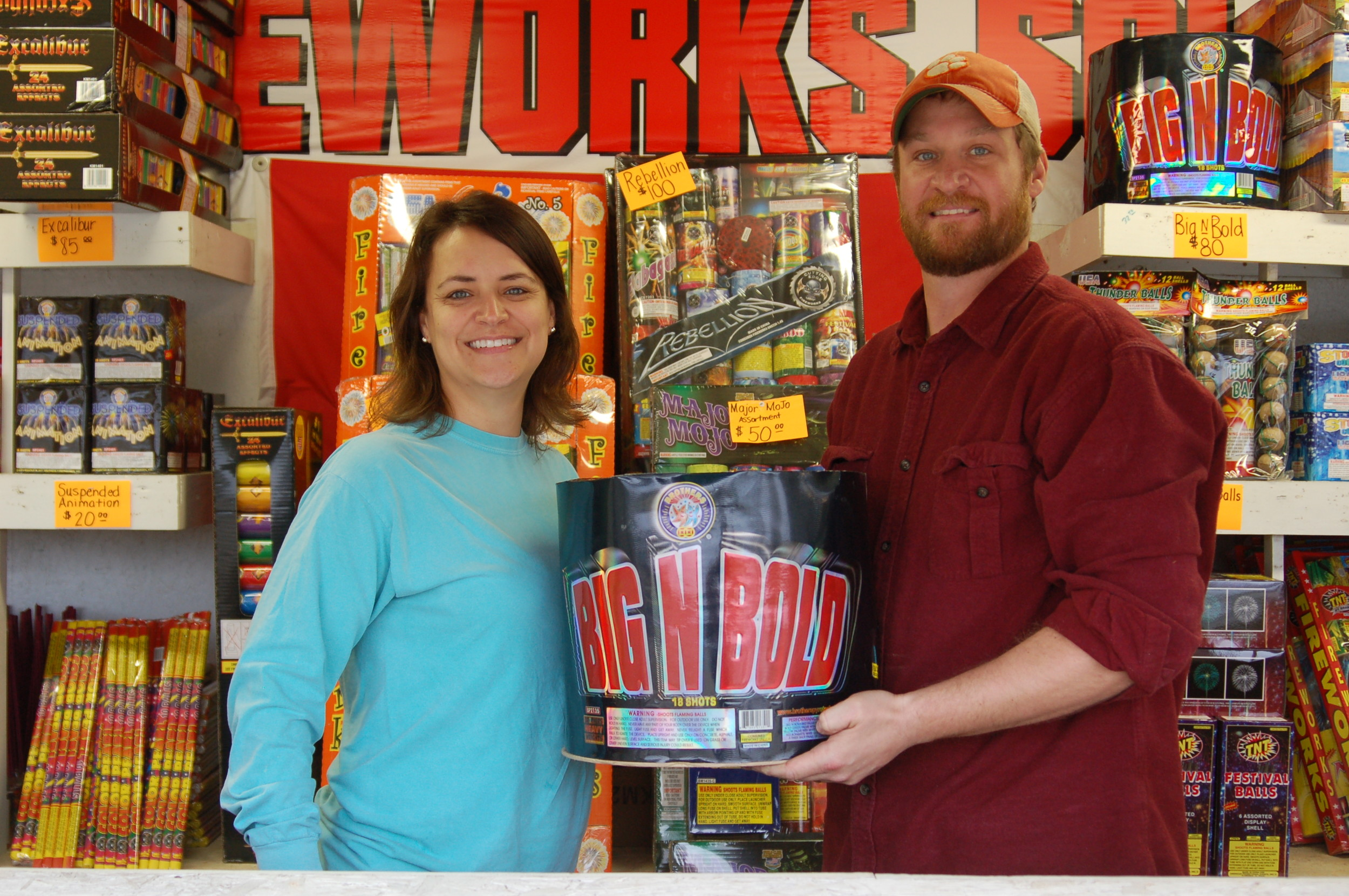 "Caroline Shorter and Justin Shorter hold a large firework ""cake"" at their firework stand near the intersection of Alex Harvin Highway and Raccoon Road on Tuesday."