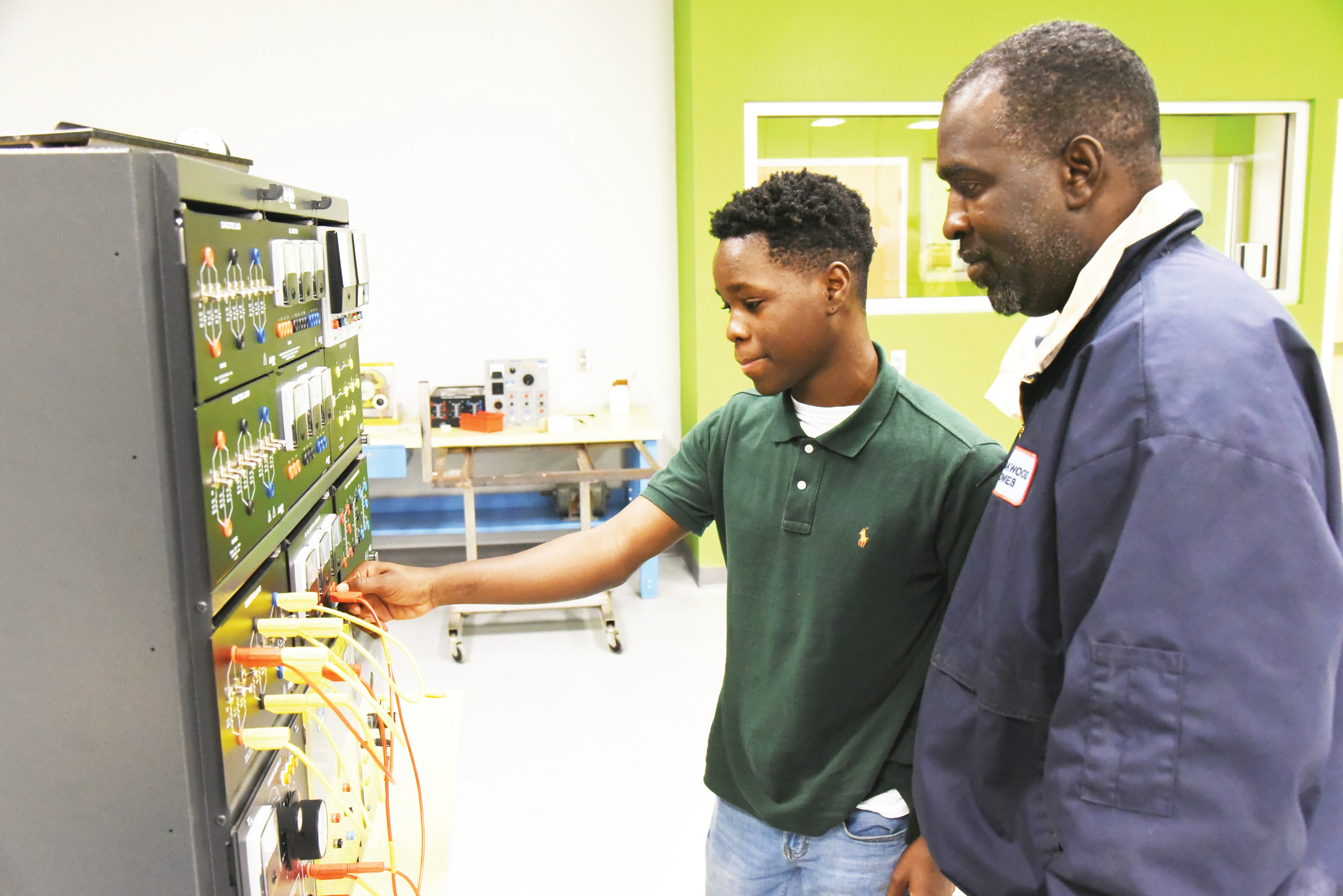 Then-Crestwood High School freshman Christopher Gooding, left, and his father, John, inspect some mechatronics classroom equipment recently at Central Carolina Technical College's Advanced Manufacturing Technology Training Center in Sumter. CCTC will start a youth apprenticeship program for high school seniors for mechatronics and machine tools.