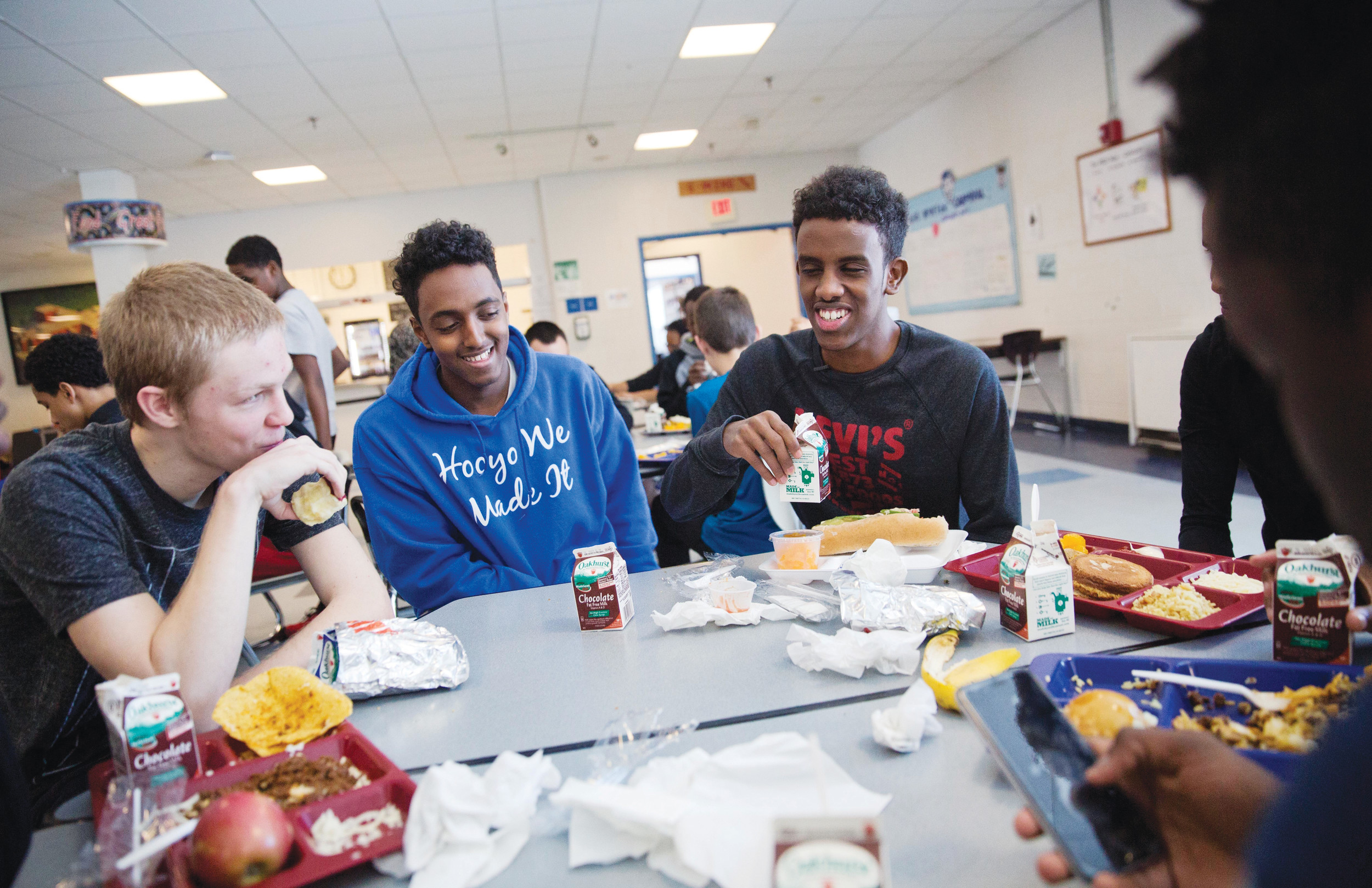 Abdiaziz Shaleh, right, a Lewiston high school senior and co-captain of the soccer team, and Essa Gedi, center, both of whose families emigrated from Somalia, sit with classmate Isiah Leach, left, during lunch in the school's cafeteria in Lewiston, Maine, in March. Two years ago, immigrant children led the high school soccer team to win the state championship, a moment heralded as a triumph for the city's embrace of its immigrant community.