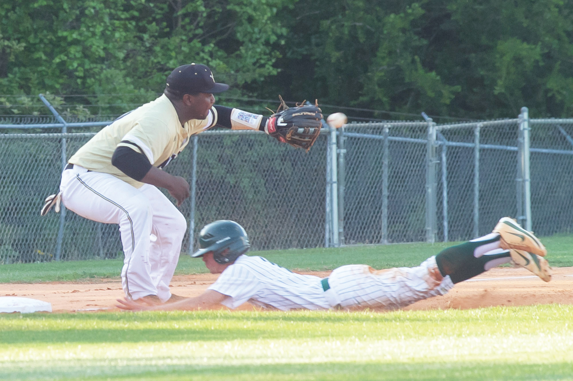 Lakewood's Wyatt Thompson, right, slides into the bag as Manning third baseman Darias Williams takes a throw in the Gators' 10-4 victory on Thursday at the LHS field.