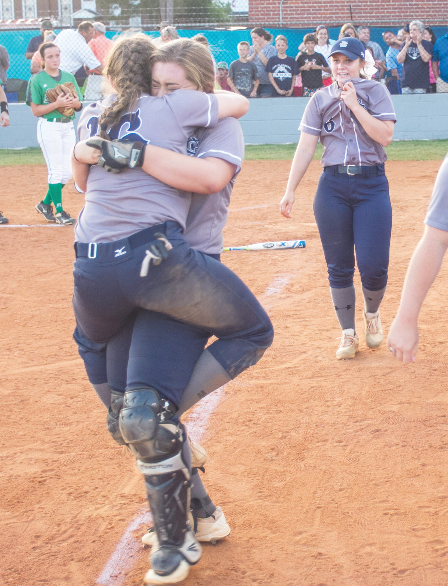 East Clarendon's Zoe McElveen (16) is hugged by catcher Abby Reardon as Marleigh Floyd (6) looks on after the Lady Wolverines defeated Dixie 4-3 in the bottom of the seventh inning on Wednesday at the ECHS field in Turbeville to claim the 1A state championship.