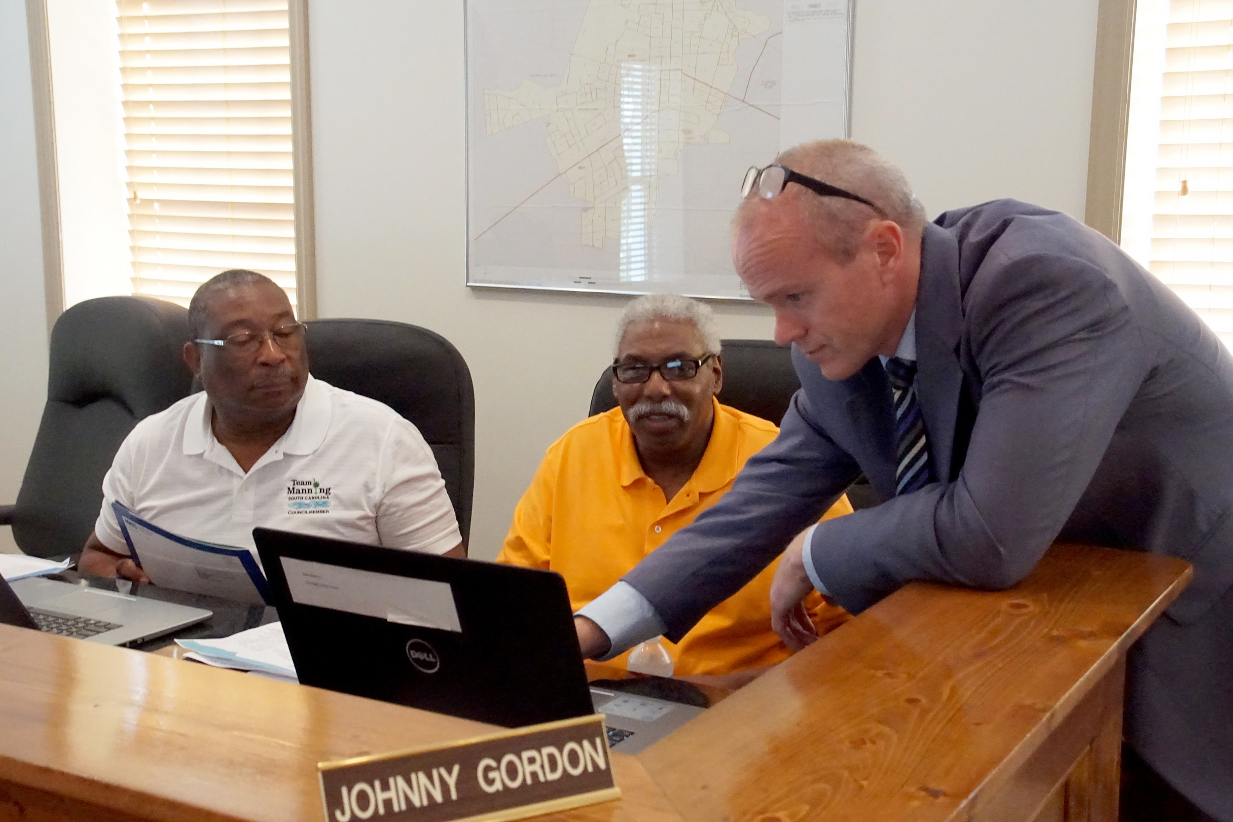 Manning City Council members Julius Dukes and Johnny Gordon watch as City Administrator Scott Tanner points out something on Gordon's computer display at Manning City Hall during Monday's council meeting.