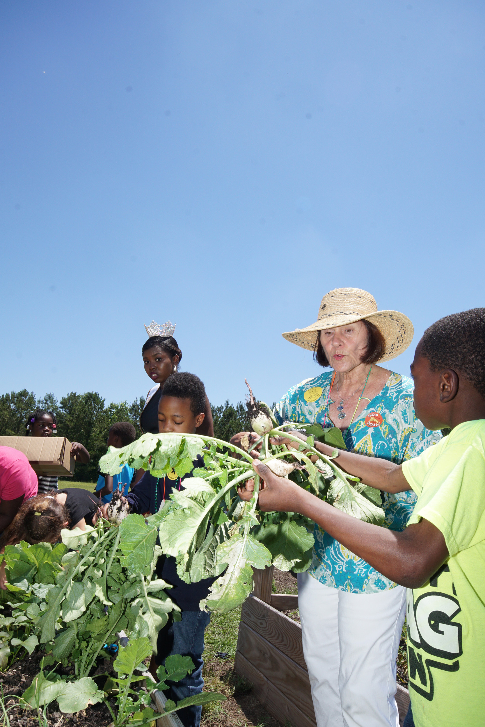 Marie Land gazes at a white radish grown by first graders at Manning Early Childhood Center as the kids harvested the garden she helped the young students plant and nurture during the spring semester.
