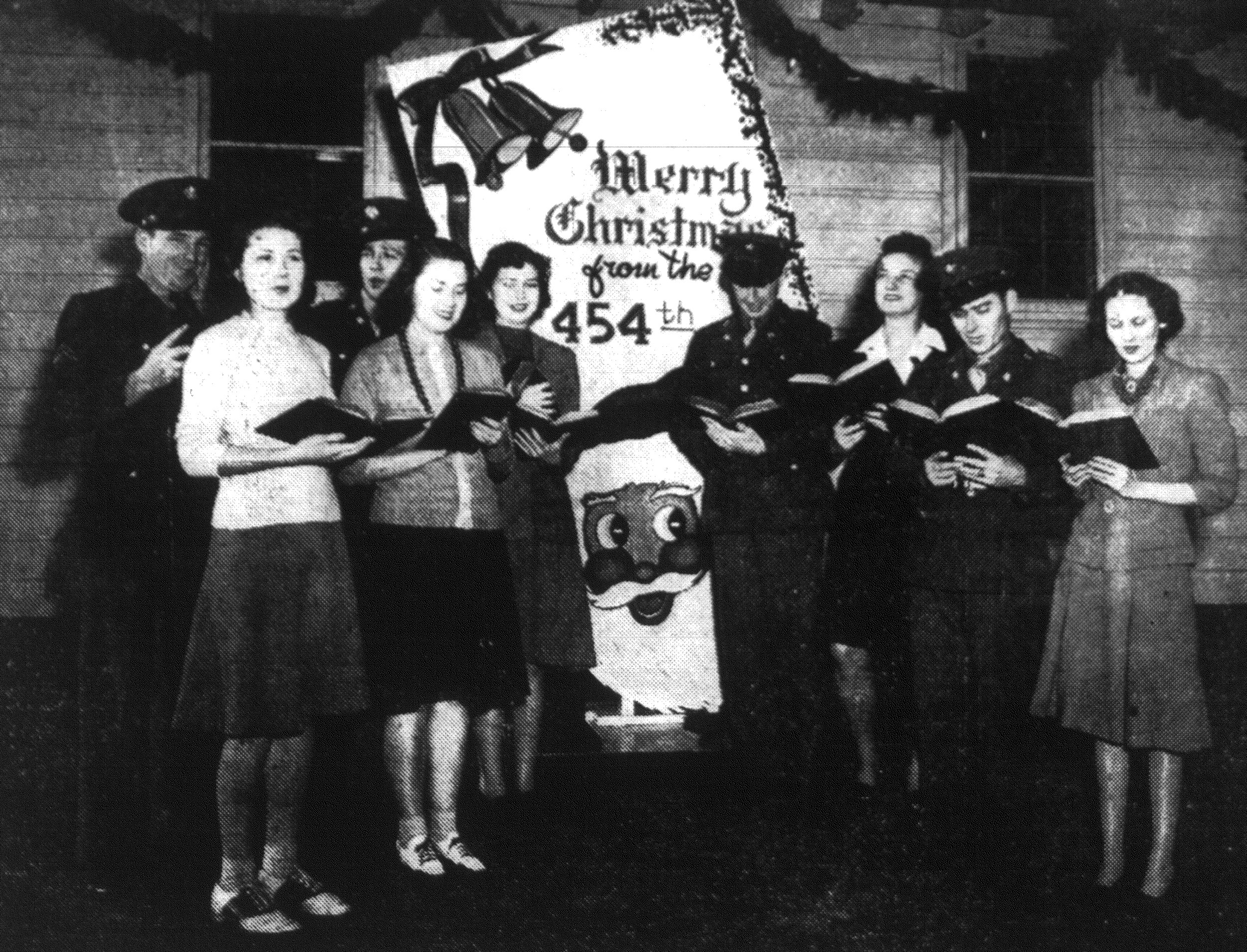 1942 - Soldiers and civilians join voices in welcoming the yuletide at the Army's Basic Flying School at Shaw Field. Gathered in front of one of the squadron dayrooms to sting out their greetings are the Missess Pansy Howell, Mary Elizabeth Rigby, Sherry Hook, Margarita Baldwin and Claire Gregg, all post headquarters employees; and Staff Sgt. Jack Lewis, Cpl. Vincent Sherwin, Cpl. Bill Jones and Pvt. Buster G. Thornton, members of the 454t Flying Training Squadron.