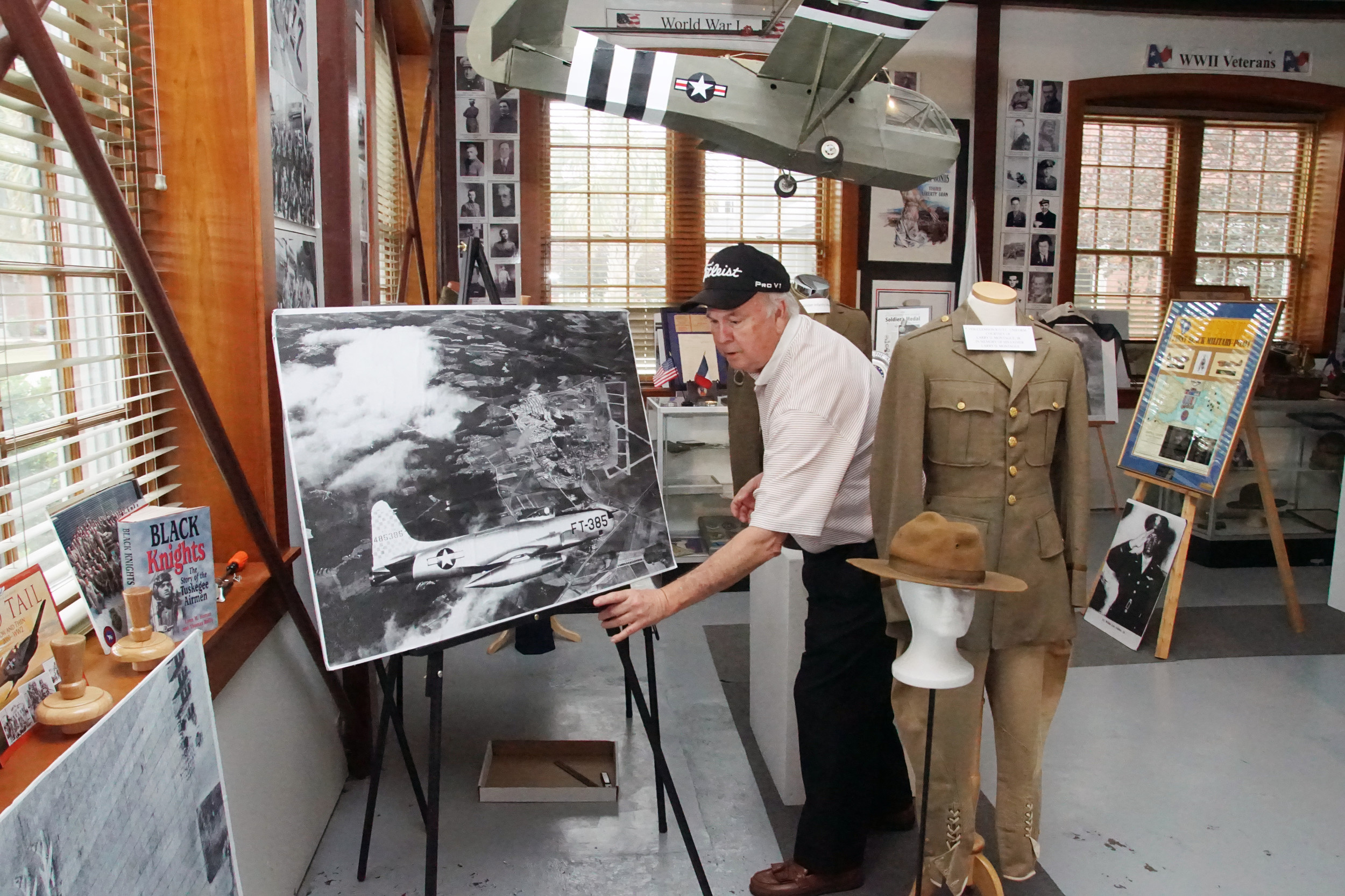 Sammy Way, director and curator of the Sumter County Military Display, adjusts a 1953 photo of one of the first jet aircraft to arrive at Shaw Field in preparation for Memorial Day. Admission to the display is free.