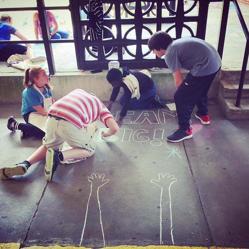 Students at Bates Middle School create sidewalk chalk art inspired by American author and illustrator Dallas Clayton.