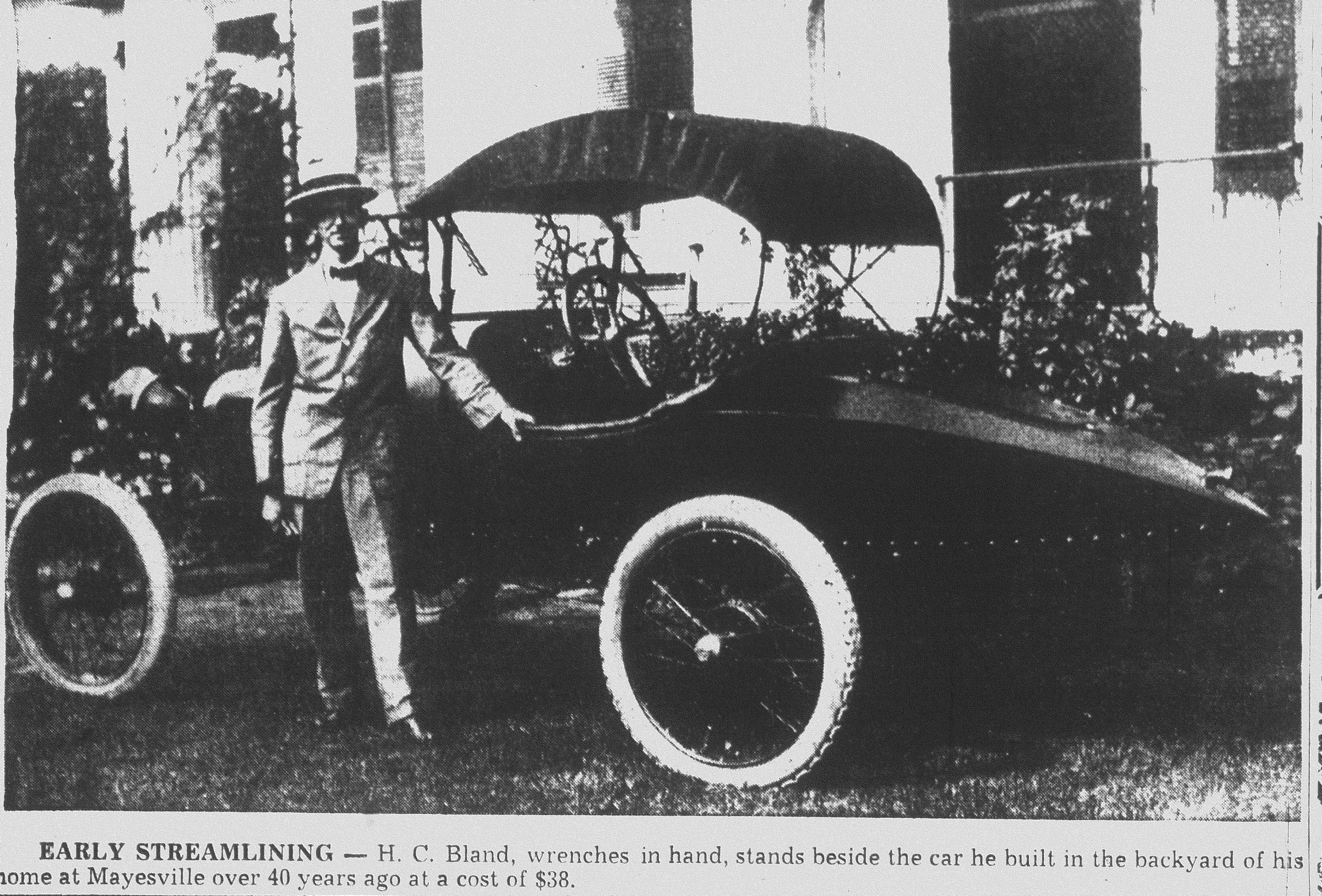 H.C. Bland, wrenches in hand, stands beside the car he built in the backyard of his home in Mayesville at a cost of $38.