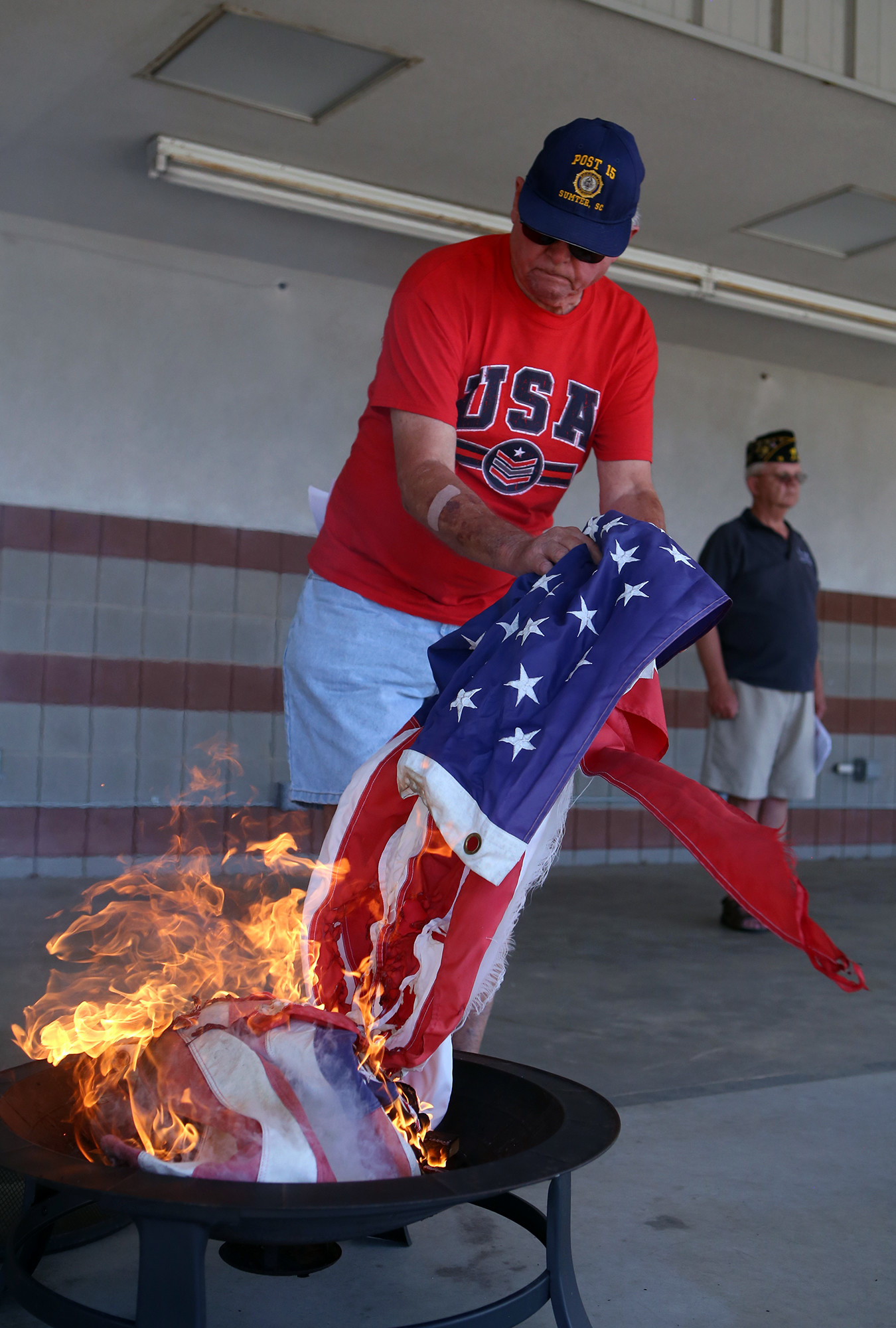 James Stokes, a member of American Legion Post 15, places a soiled flag onto the fire for a proper disposal during the Post's 2015 Flag Day ceremony.