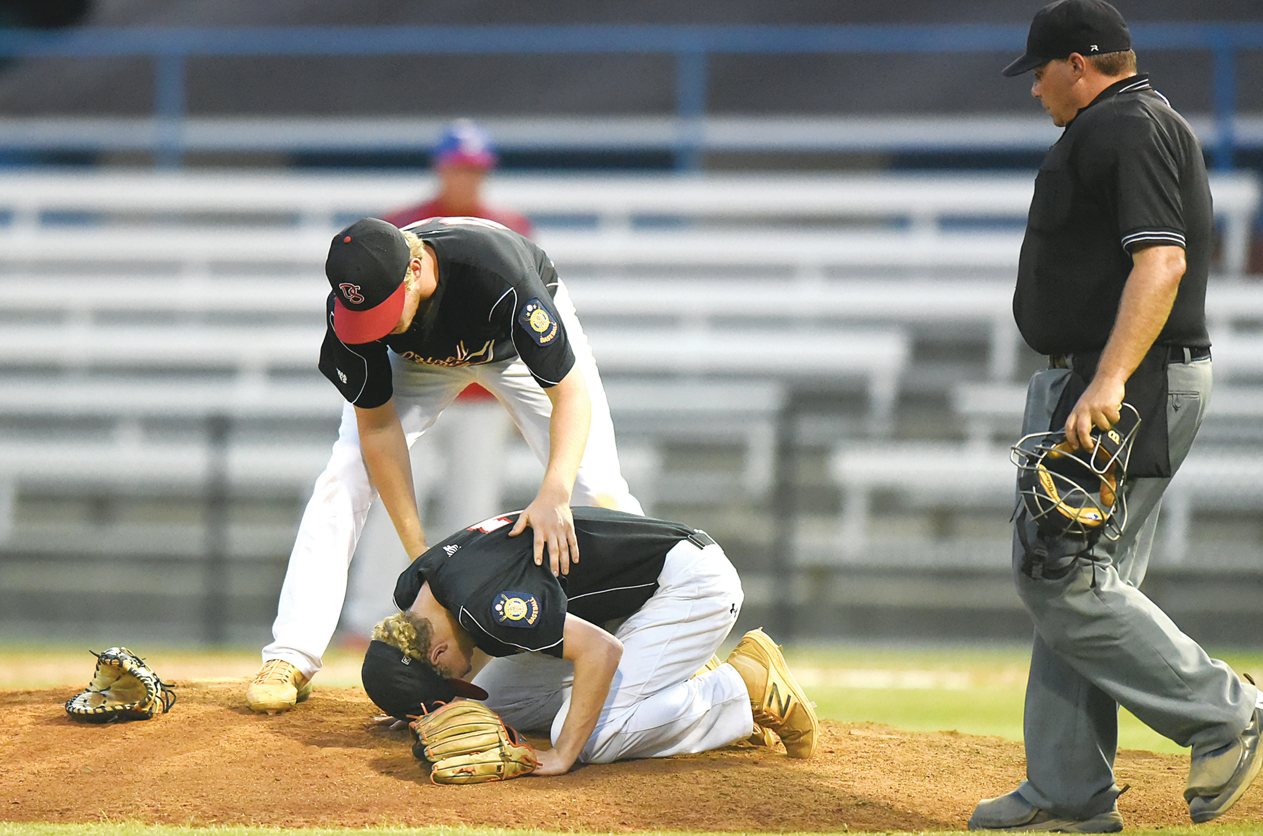 Players, umpires and coaches rush to the aid of Dalzell-Shaw relief pitcher Chris Parrish when a throw from the catcher for second base hit him during the Jets' 11-1 loss to Sumter on Monday at Riley Park. Parrish had to leave the game