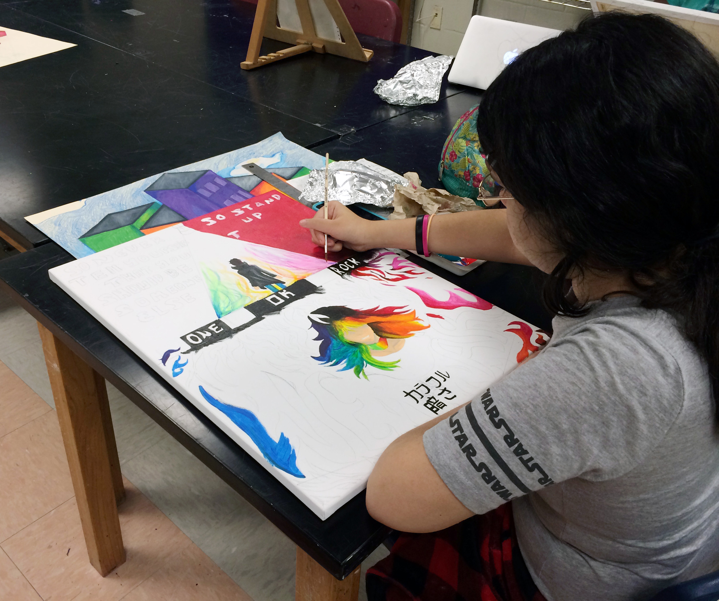 "Sylvia Zaragoza, a 10th-grader at Crestwood High, works on her painting titled ""We Are"" in Crystal Chambers' class during the REACH Summer Arts class. She said the class was given the option of painting people, bands, an object or several other subjects for this assignments."