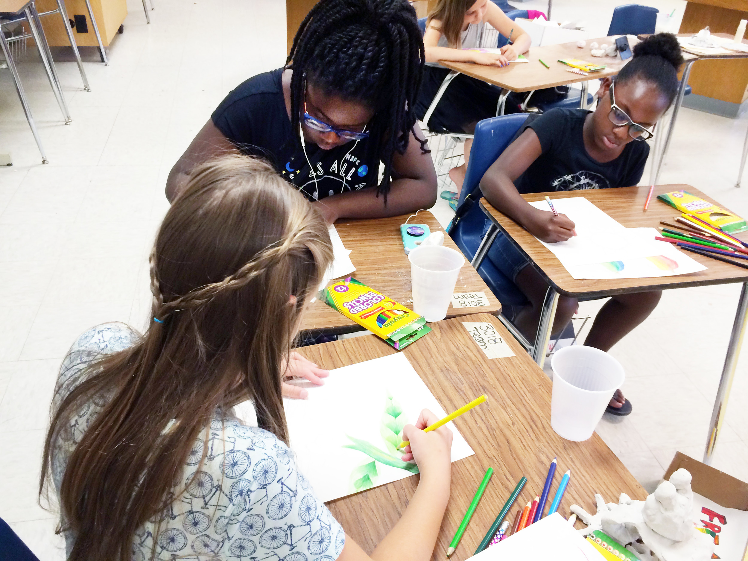 From left, Leah Page and Ava Breland, both rising fifth-graders at Millwood Elementary School, and Mariah Williams, a rising fourth-grader, also attending Millwood, work on their art inspired by the Beatles in Laura Cardello's art class.