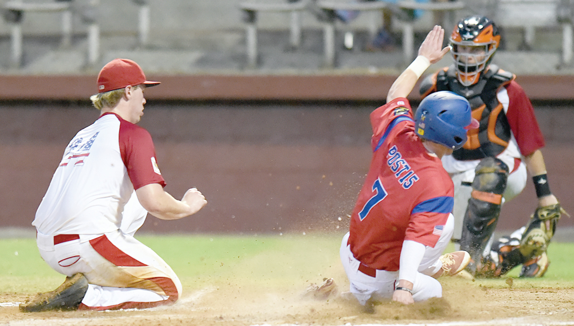 Sumter second baseman Ryan Moore (7) scores a run on a wild pitch as Wilmington, N.C., pitcher Mike Gang, left, is late getting to the plate during the P-15's 12-2 victory on Saturday in the North/South Tournament of Champions at Riley Park.