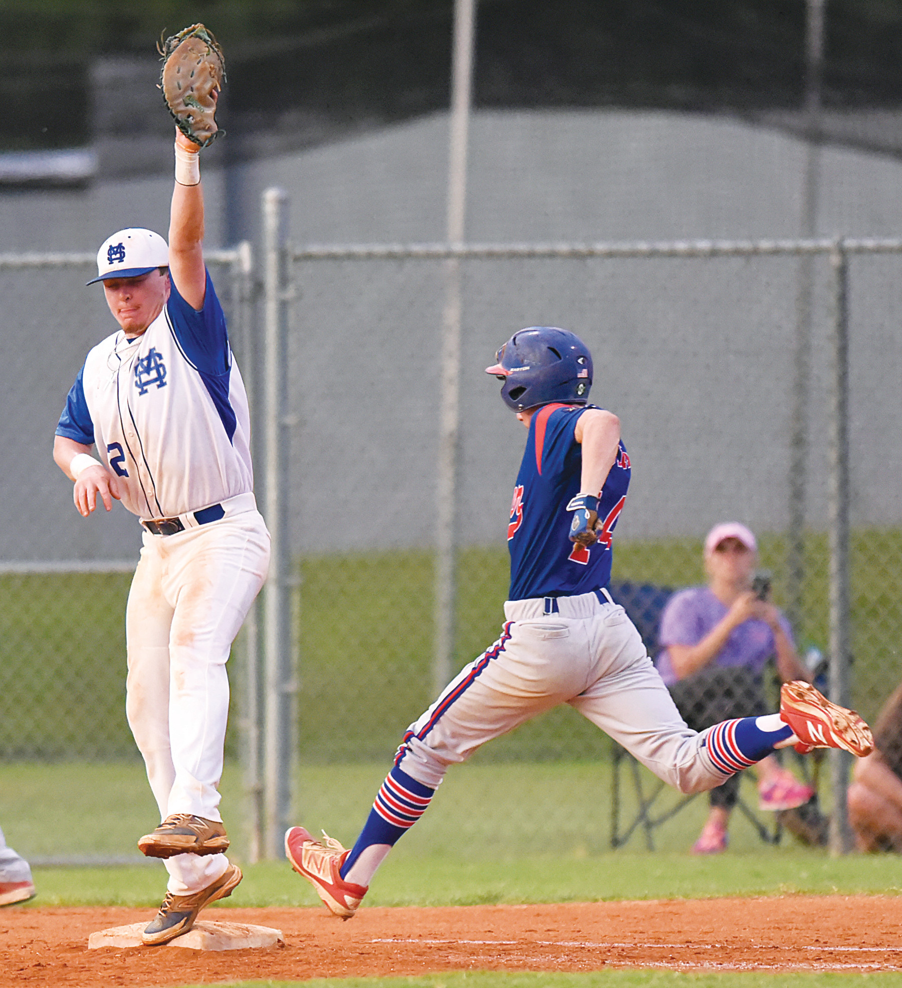 RICK CARPENTER / THE SUMTER ITEM  Manning-Santee first baseman Trent Frye reaches high for a throw as Sumter's Ryan Touchberry races to first on an infield hit in the P-15's 14-2 win on Tuesday at Monarch Field in Manning.