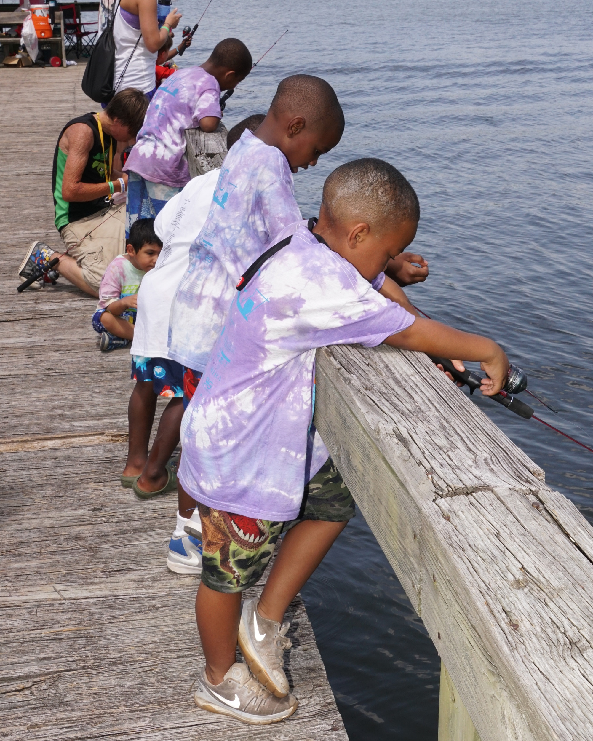 A group of the young campers at Camp Happy Days try their luck at fishing at Lake Marion.