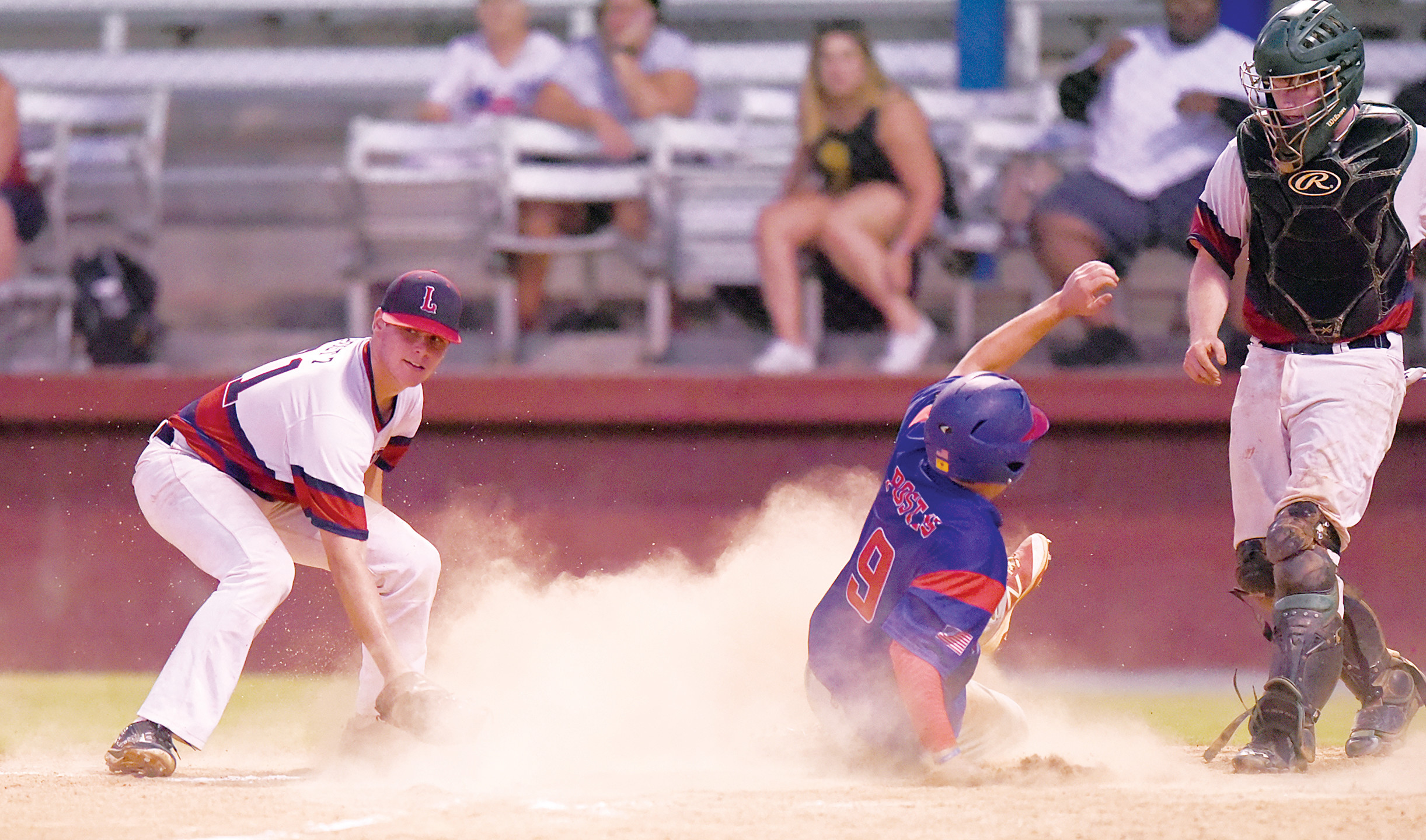 Sumter third baseman Joey Pereira (9) slides safely into home on a passed ball as Lexington pitcher Jon Scott, left, covers the plate in the P-15's 10-1 win in the opening game of the second-round state playoff series on Wednesday at Riley Park.