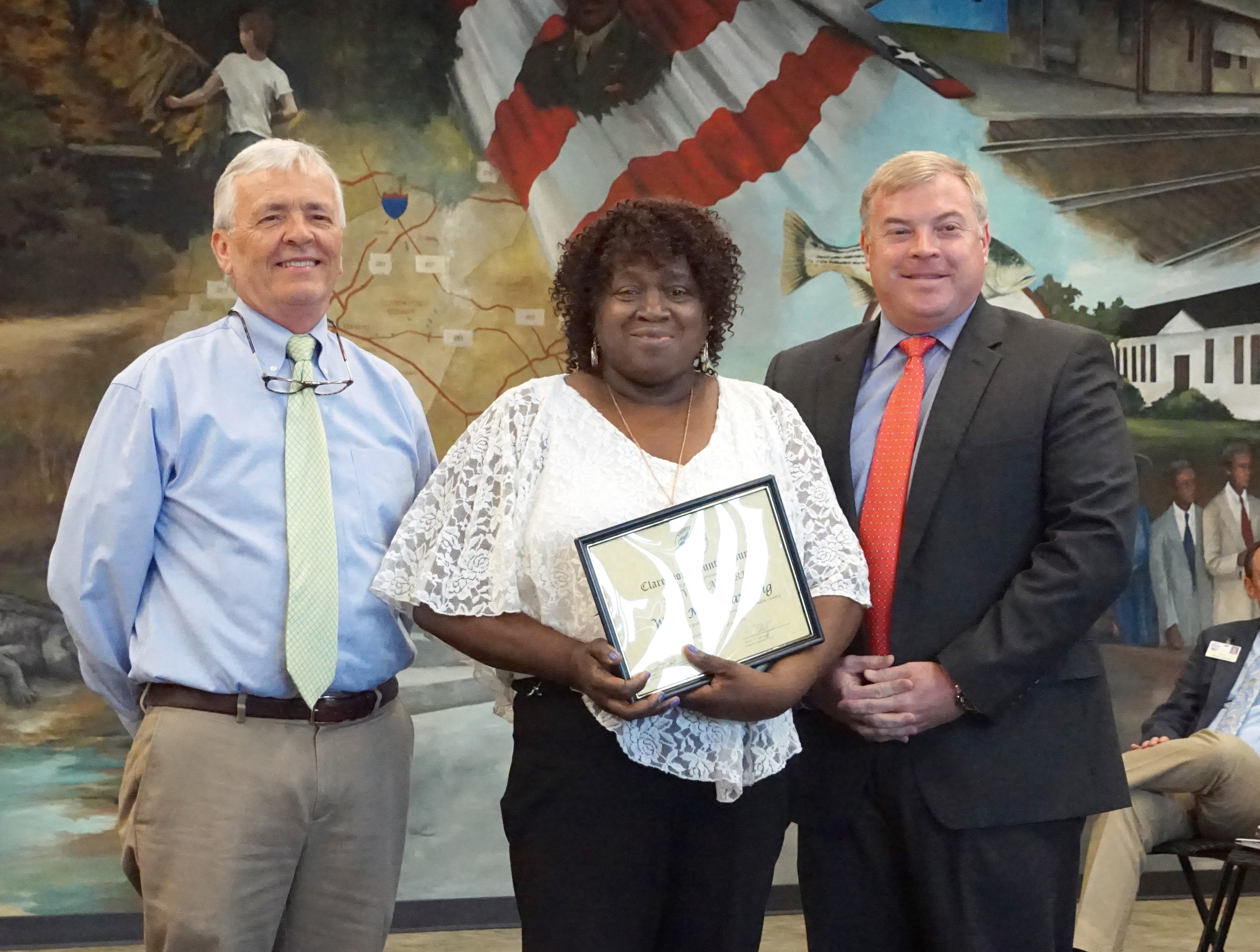 Willa Mae Manning, assistant supervisor with Clarendon County Communications E-911, receives a certificate and clock in recognition of her 25 years of service from Clarendon County Council Chairman Dwight Stewart and County Administrator David Epperson.