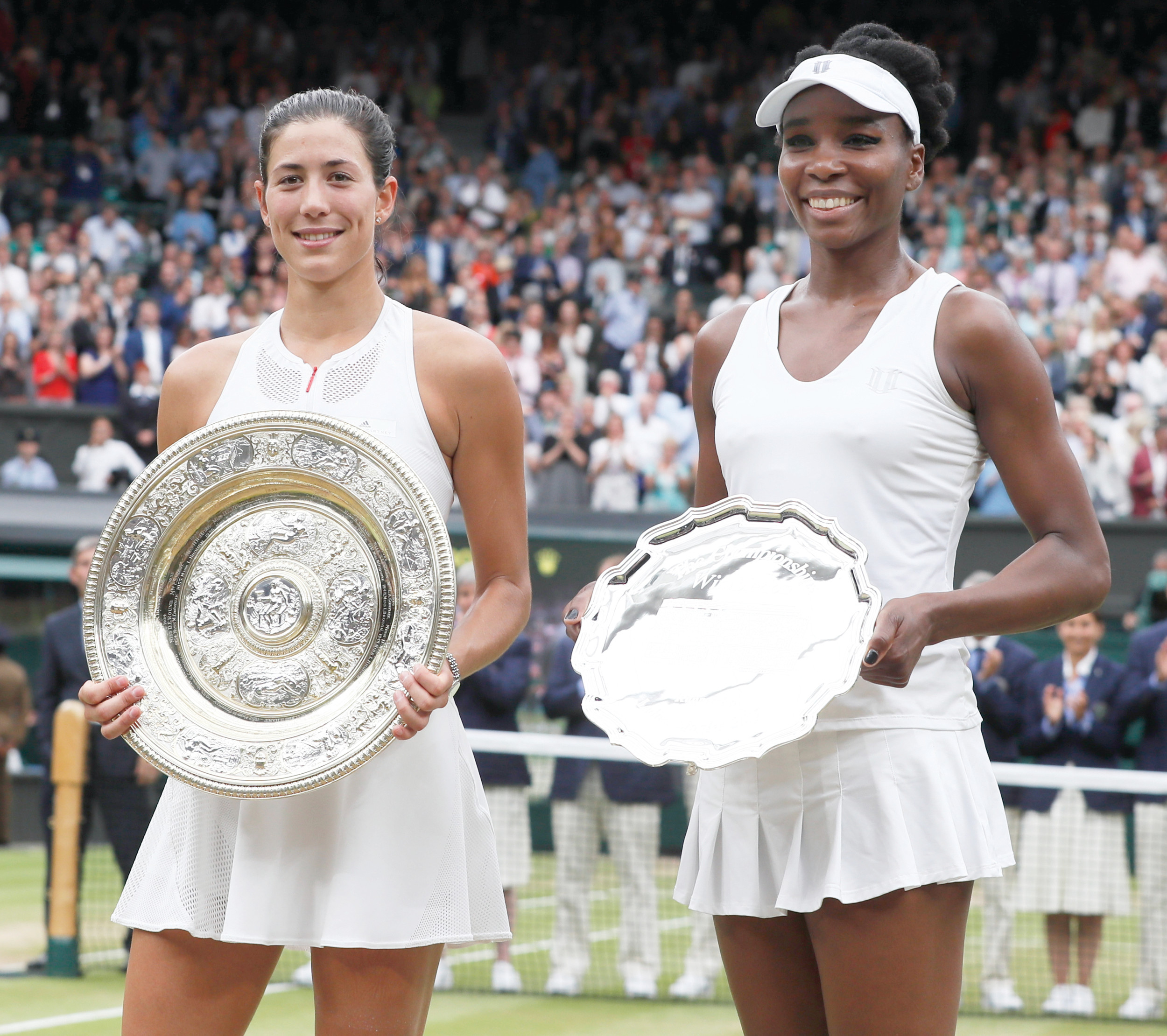 Garbine Muguruza, left, holds the winners trophy after defeating Venus Williams 7-5, 6-0 in the Wimbledon women's singles final on Saturday in London.