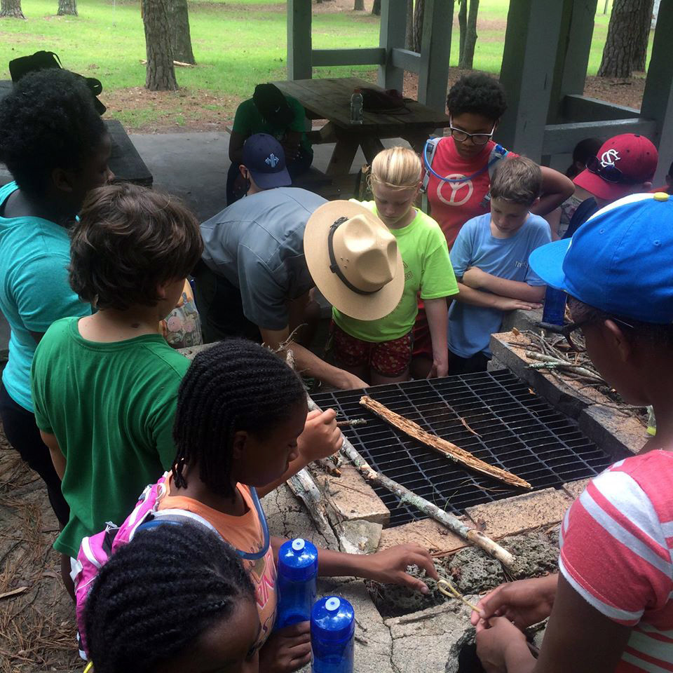 Students at a past 4-H2O camp listen and watch as a forest ranger talks to them about the importance the ecosystem.